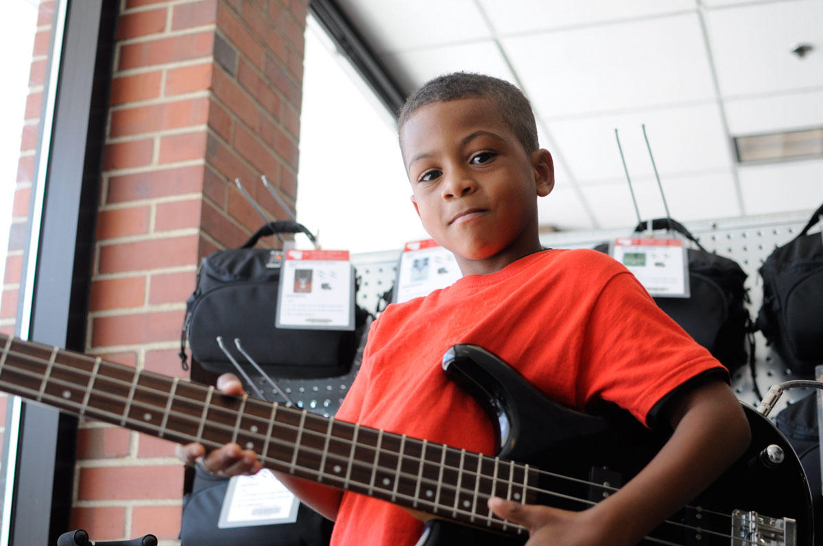Picture of a kid holding a guitar from AADL's collection