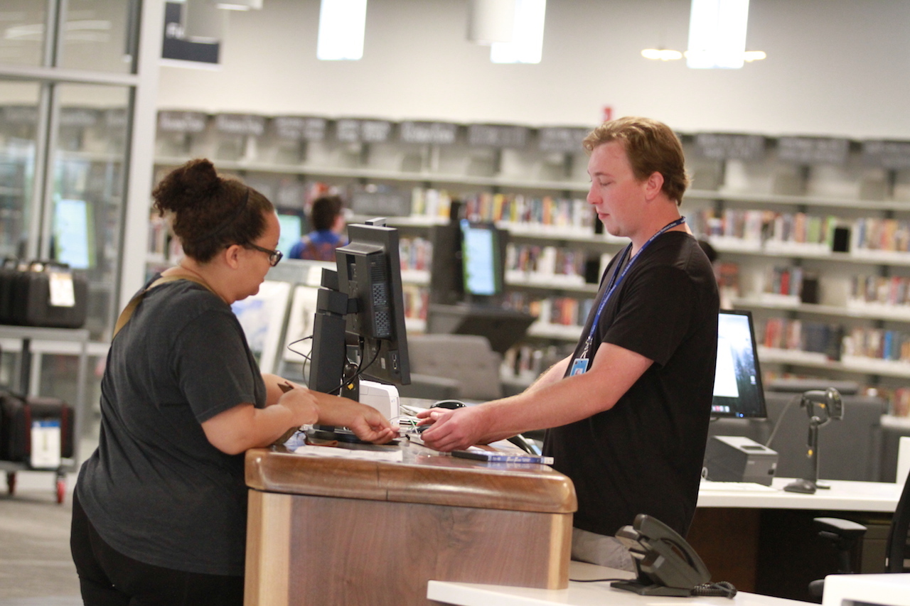 A library users gets help at the info desk.