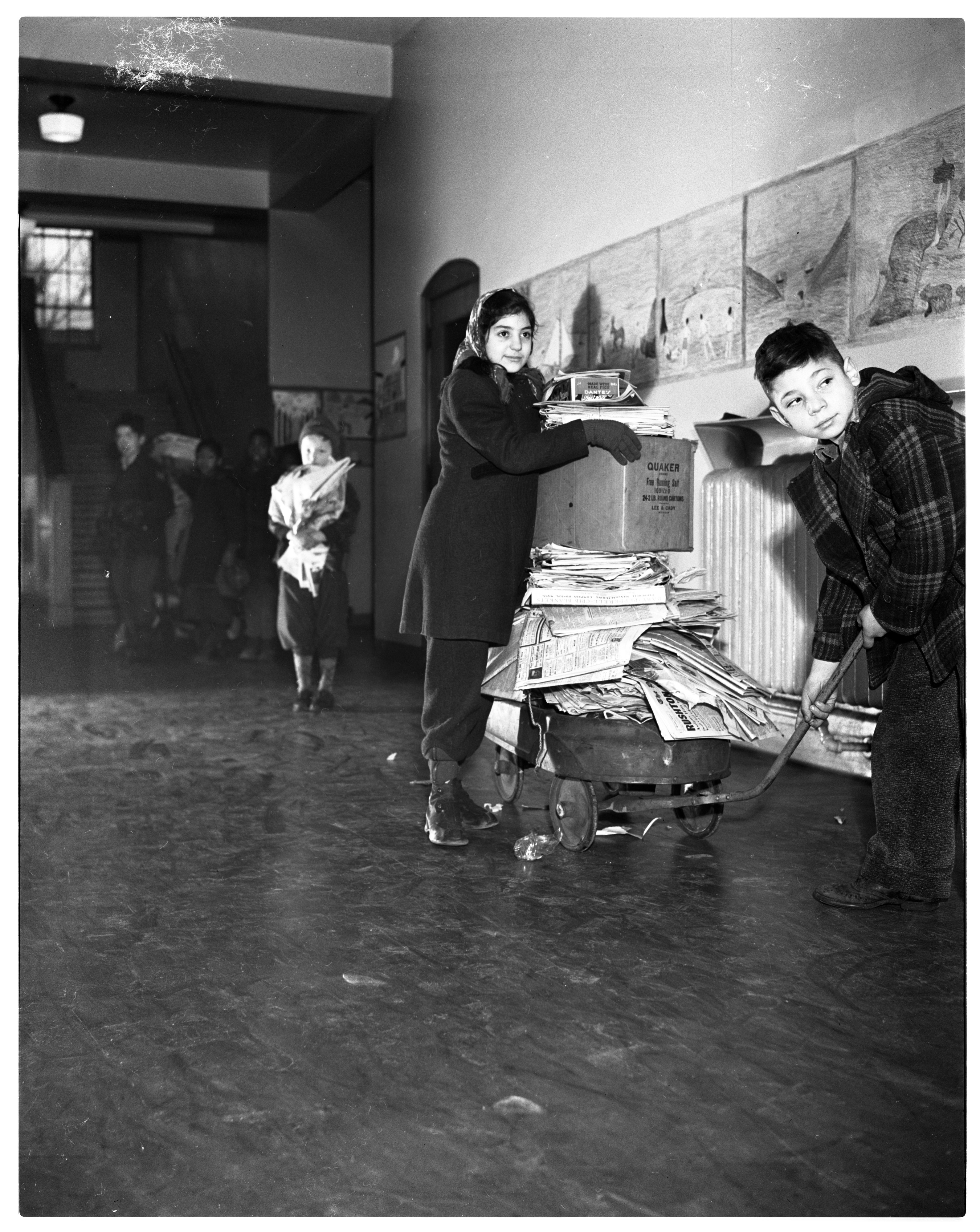 Children with wagons and piles of paper