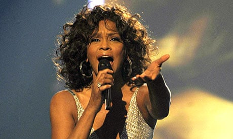 Whitney Houston sings into a microphone