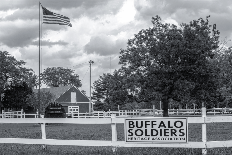 The Buffalo Soldiers Heritage Association sign hangs on the white wood fence that surrounds the paddock. An American flag on a flagpole and the stables are in the background.