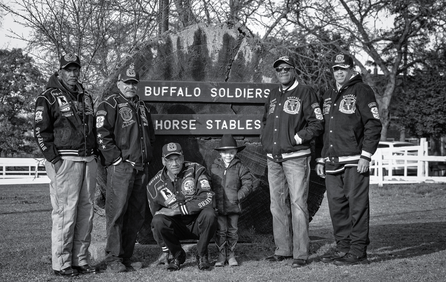Five adult members of the Detroit BSHA and a young boy stand in front of the monument sign.