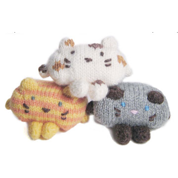 Three knitted stuffed cats in a pile