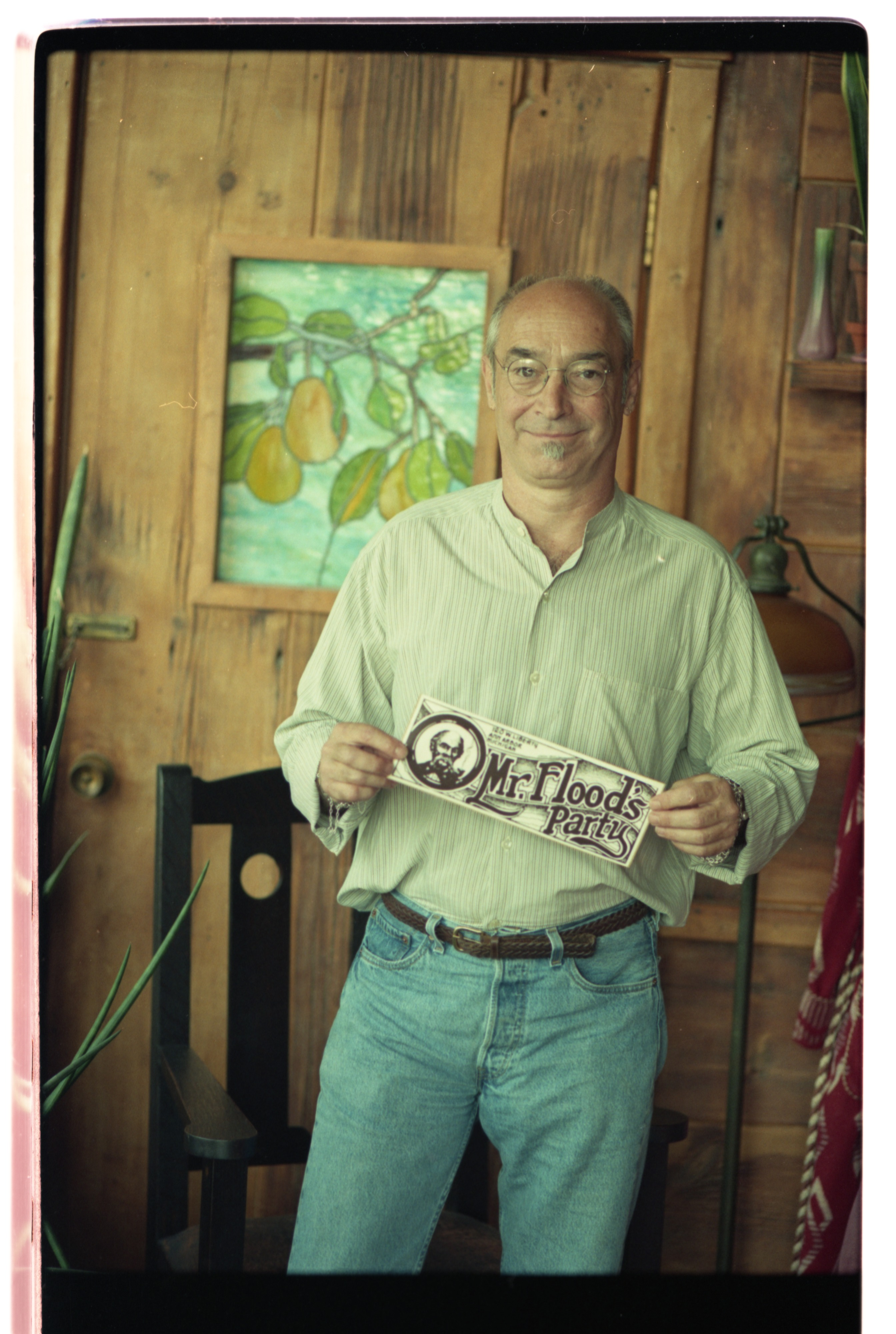 Ned Duke Displays A Mr. Flood's Party Bumper Sticker, August 1998 image