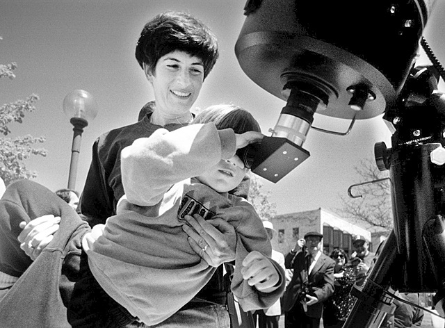 Elizabeth Schwartz Helps Her Son, Nicholas, Look Through A Telescope To View The Solar Eclipse, May 10, 1994 image