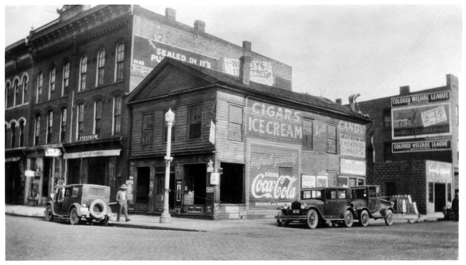 The corner of Ann St. & Fourth Ave. with a Greek Revival building on Ann St. and a Colored Welfare League sign on the Kayser image