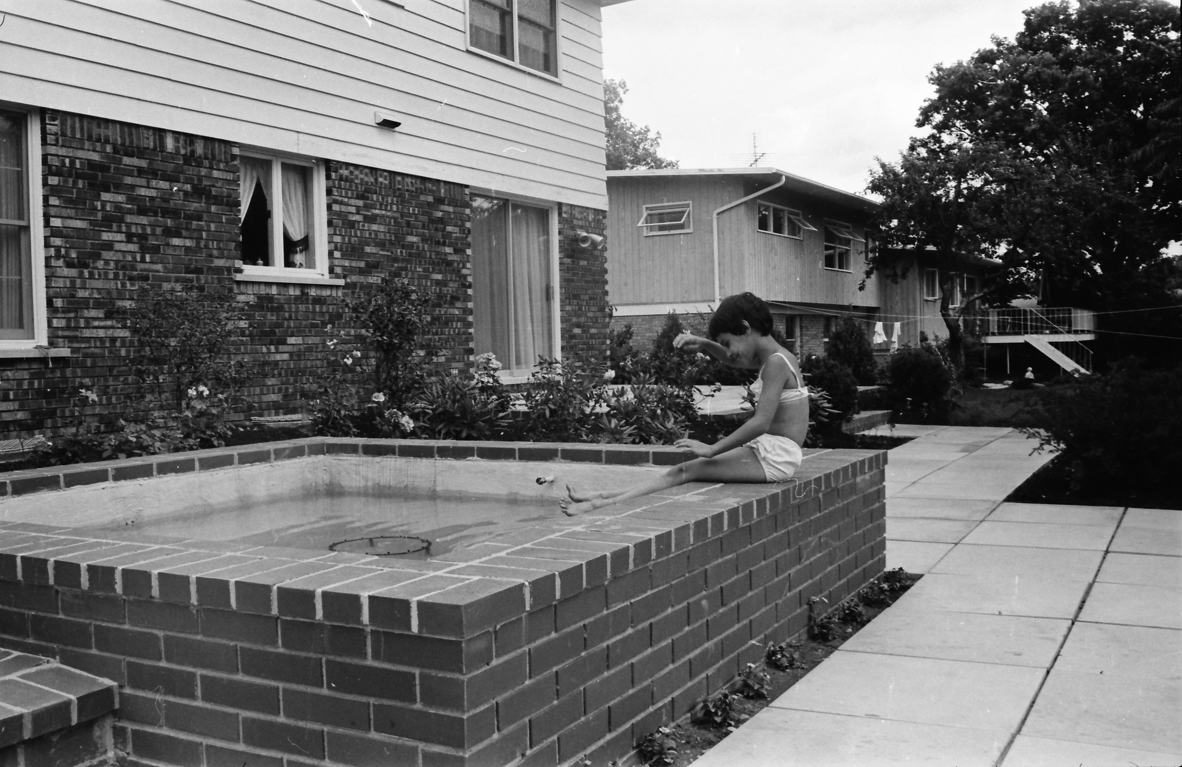 Young Child Sitting on the Edge of Small Outdoor Pool, July 1968 image