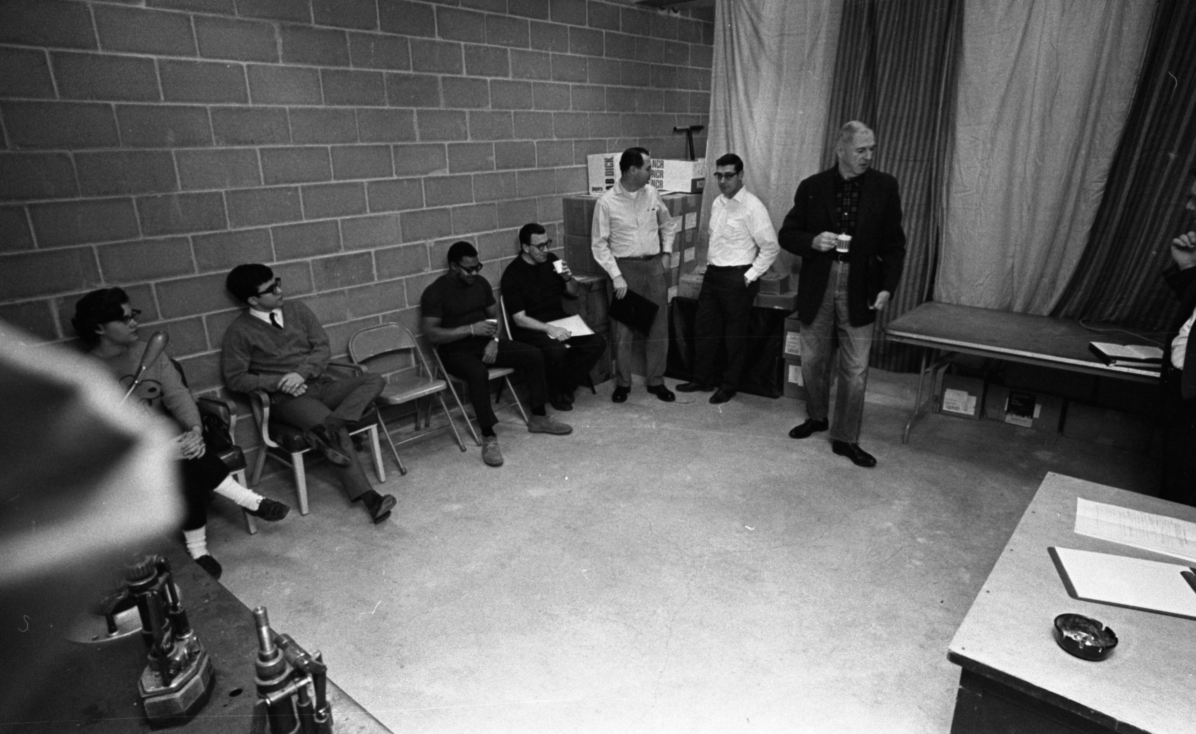 Ann Arbor News reporter Dennis Chase (left) joins group in fallout shelter for civil defense test, February 1969 image
