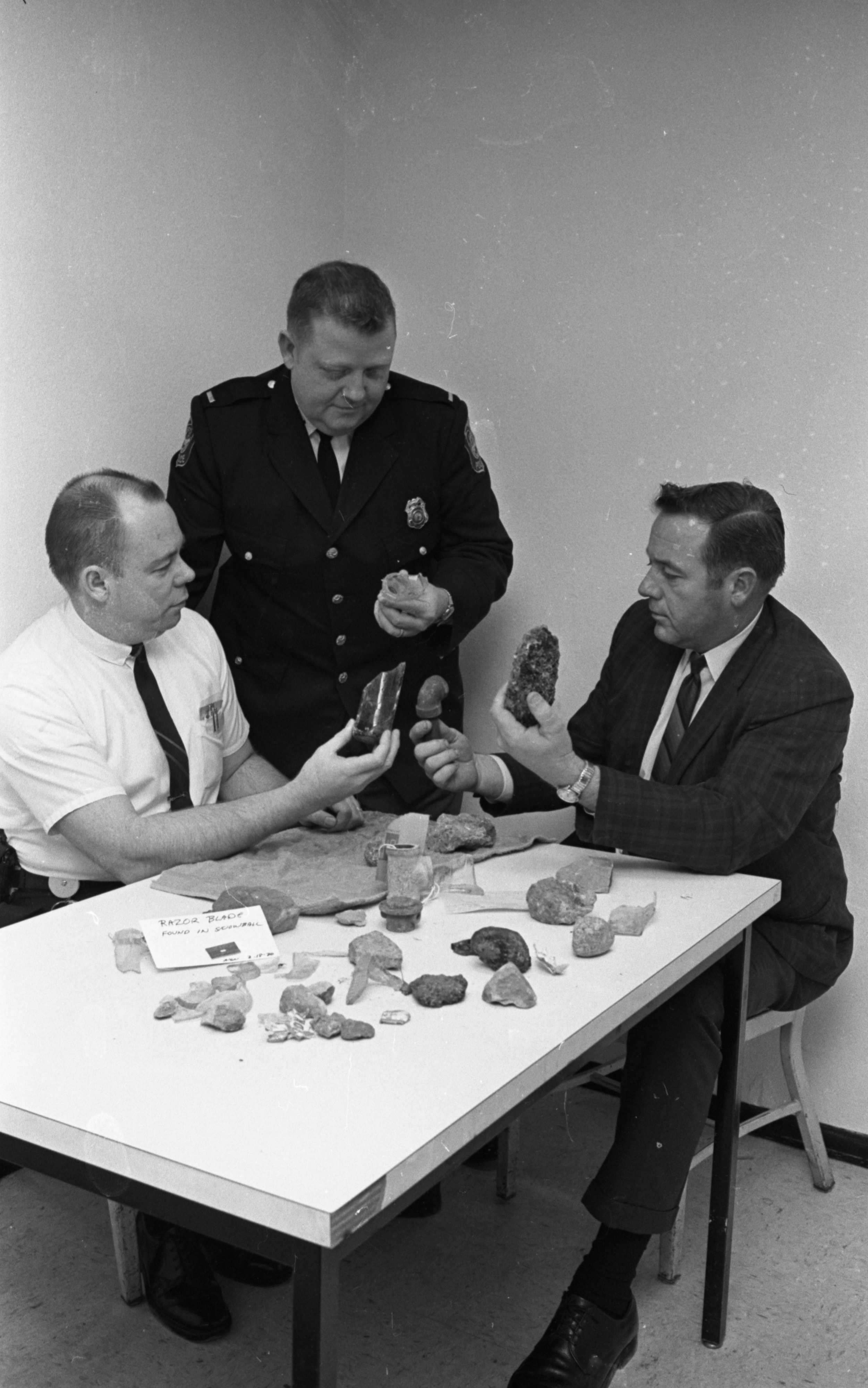 Ann Arbor Police Officers Examine Rocks Hidden In Snowballs, February 1970 image