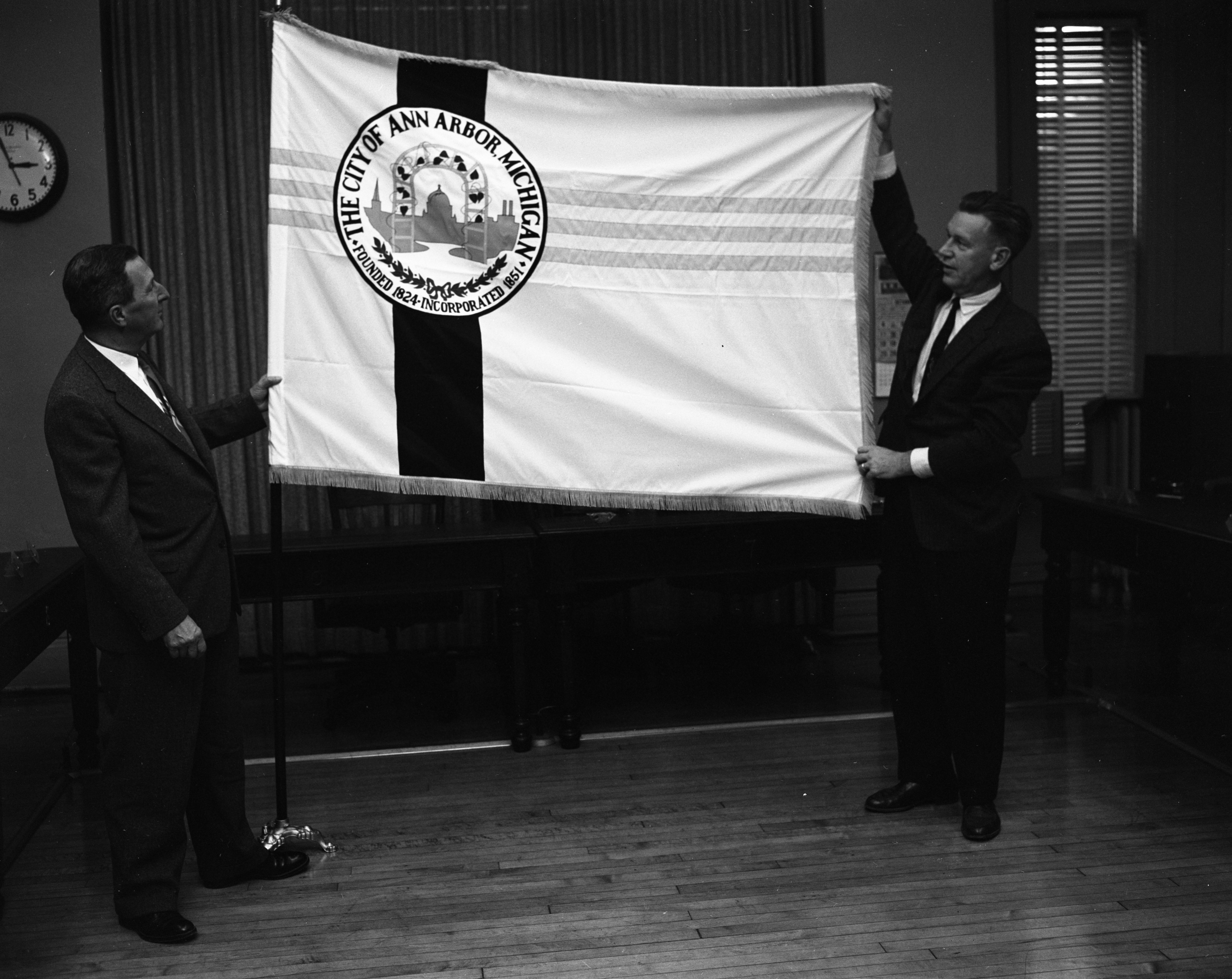 City Clerk Fred J. Looker (left) and City Administrator Guy C. Larcom Jr. examine the new city flag at City Hall, October 1959 image