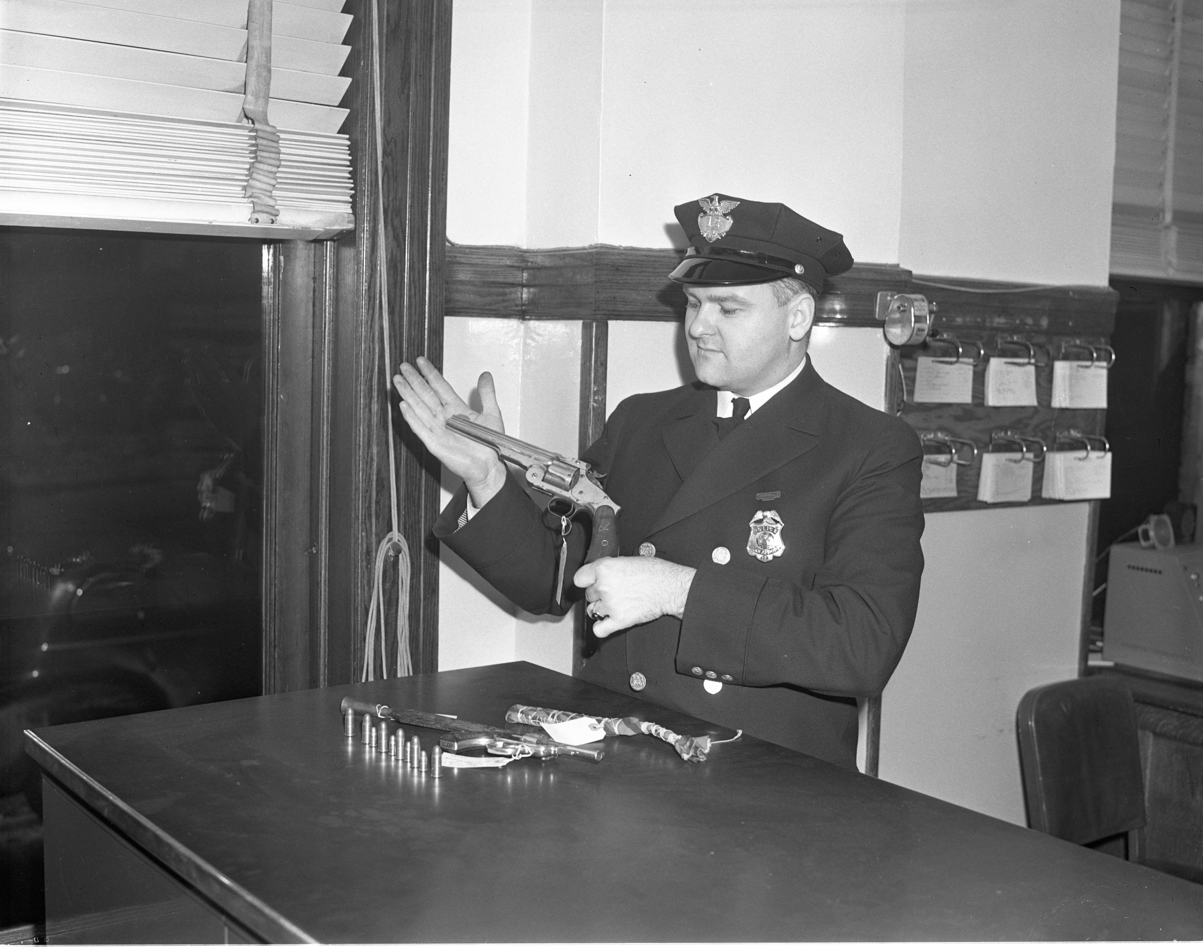 Ann Arbor Police Patrolman Rolland Gainsley Examines A Revolver, January 1941 image