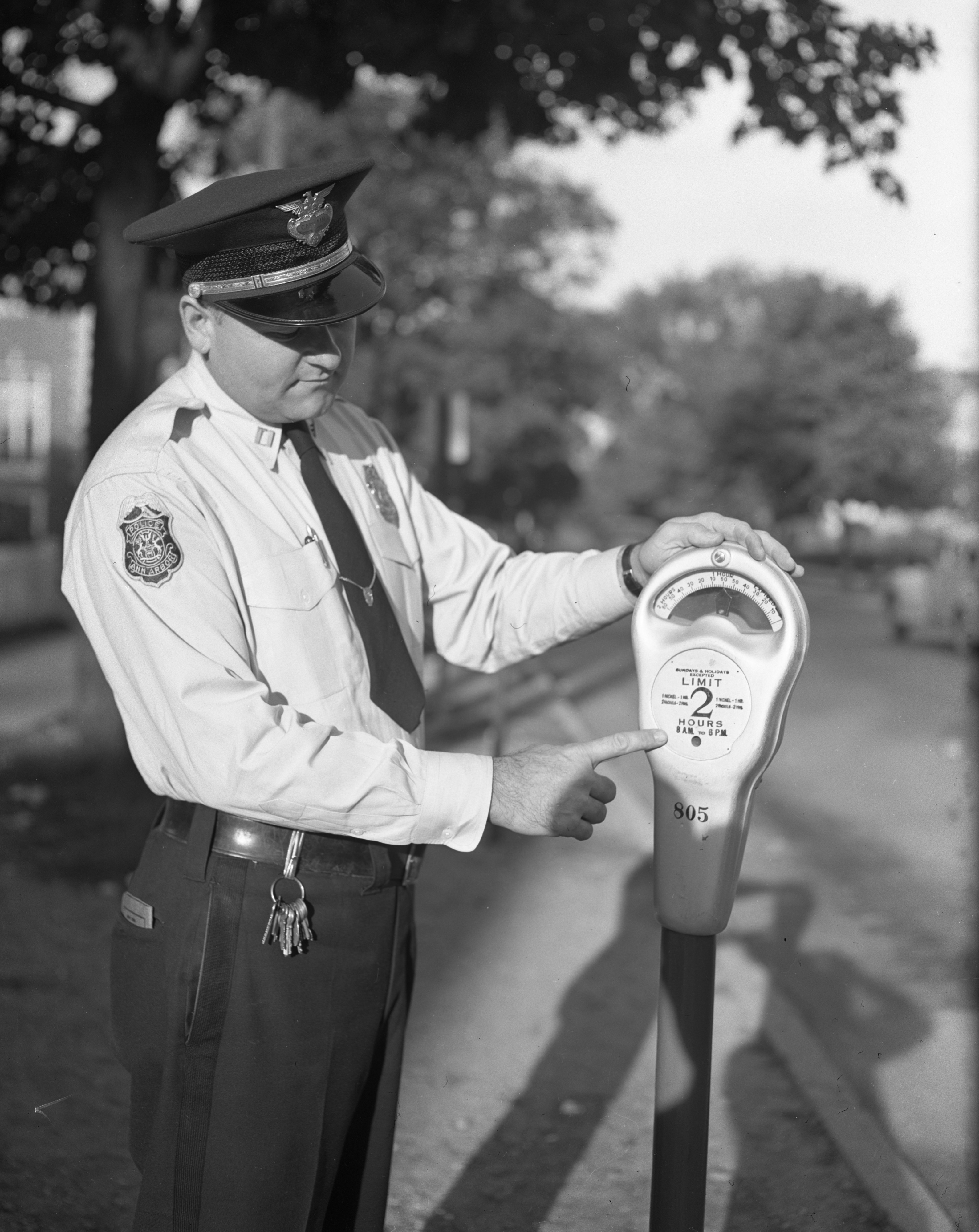 Ann Arbor Police Capt. Rolland Gainsley Demonstrates New Two-Hour Parking Meter, September 1948 image