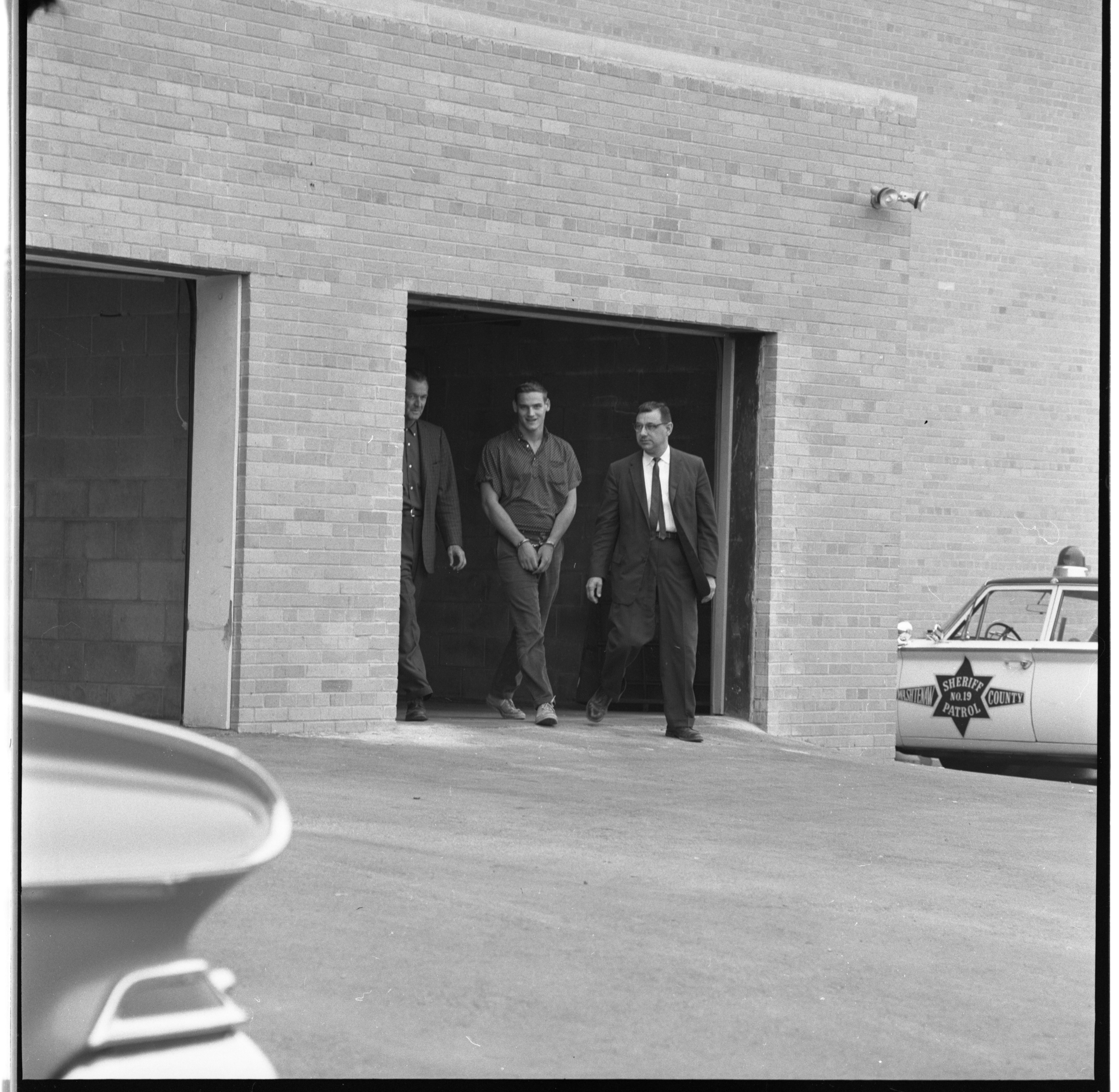 Washtenaw County Sheriff's Detectives Escort Armed Robbery Suspect To Municipal Court, July 1961 image