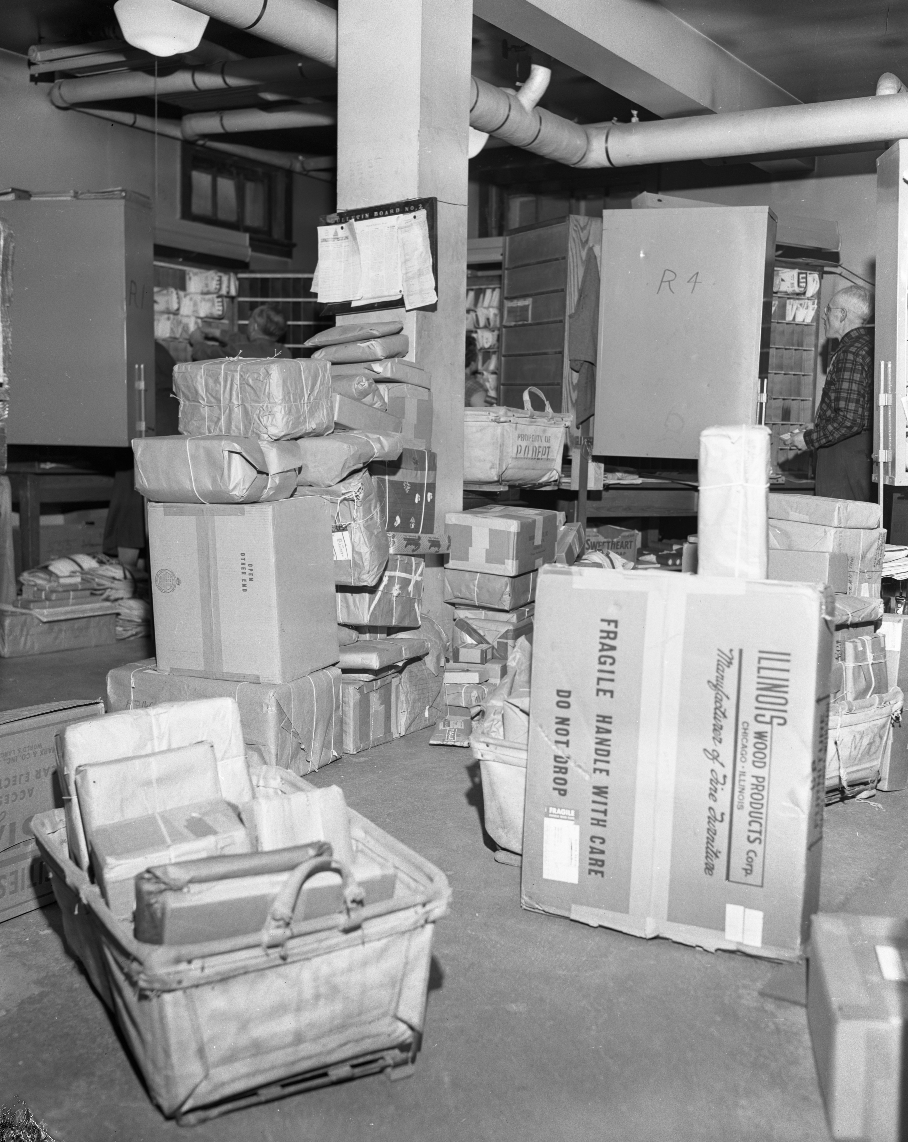"Accumulated parcels in the ""rural room"" of the N. Main St. Post Office, December 1955 image"