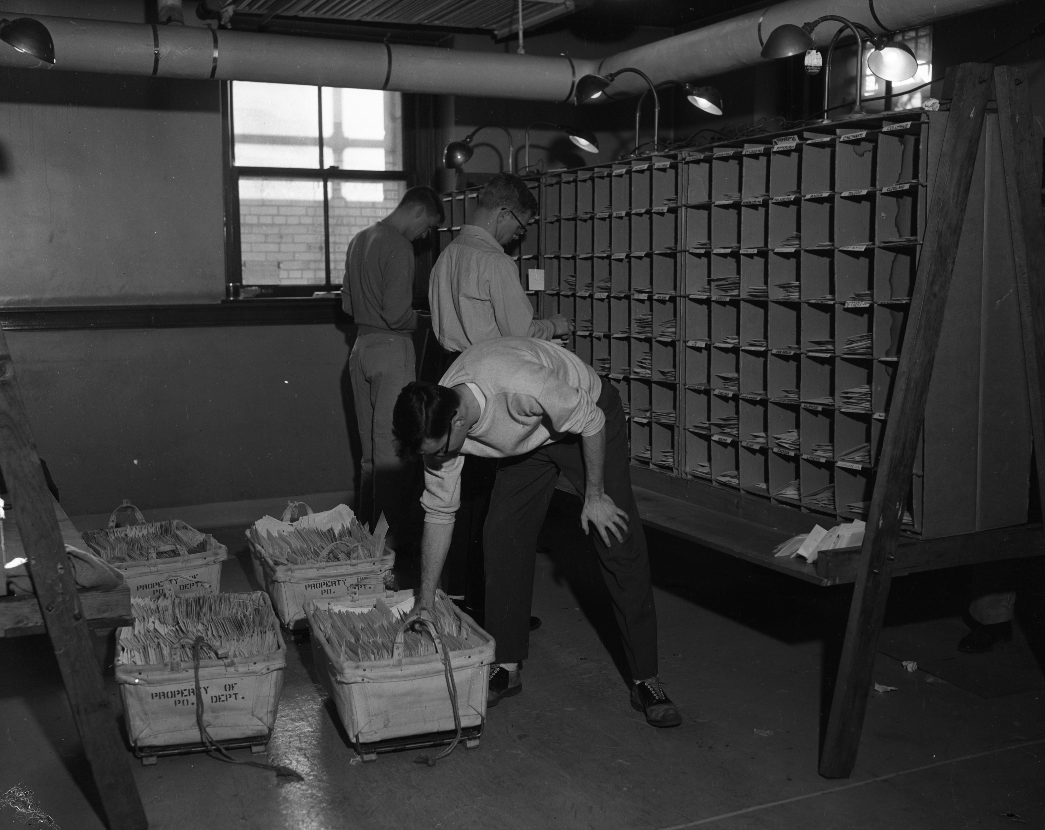 Part-time workers sort mail at the Ann Arbor Post Office during the Christmas season, December 1955 image
