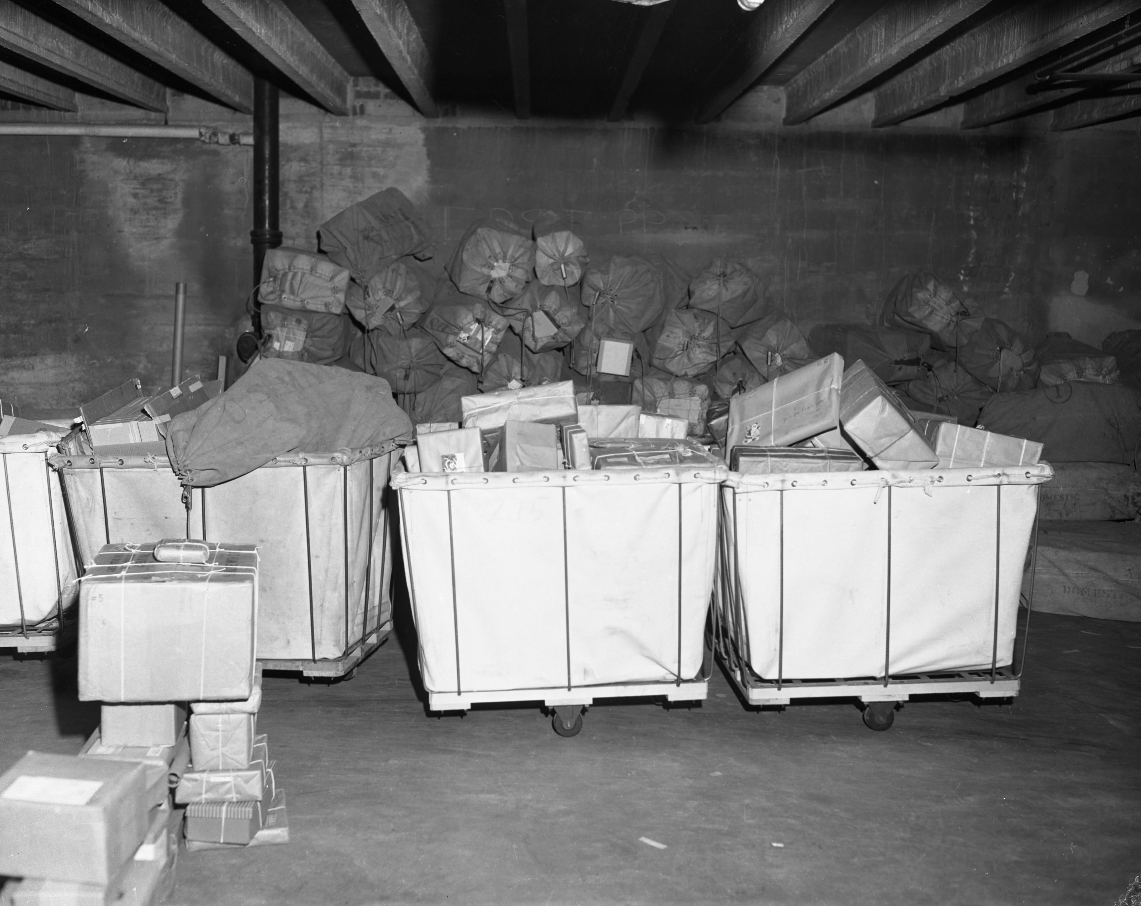 Holiday packages ready for shipment sit in the basement of an office building at N. Main and Depot Sts, December 1955 image