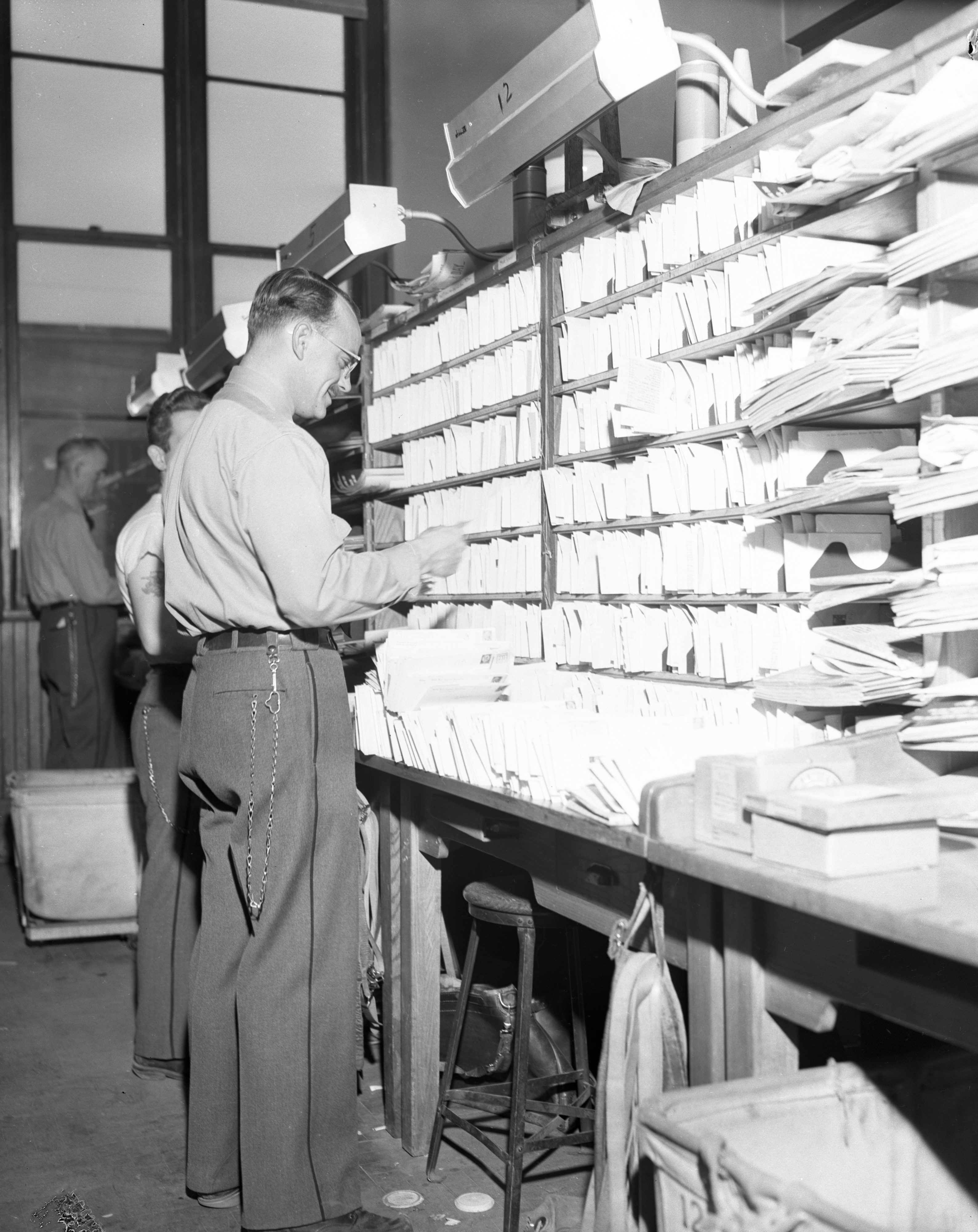 A postman looks over his load at the Ann Arbor Post Office during Christmas rush, December 1955 image