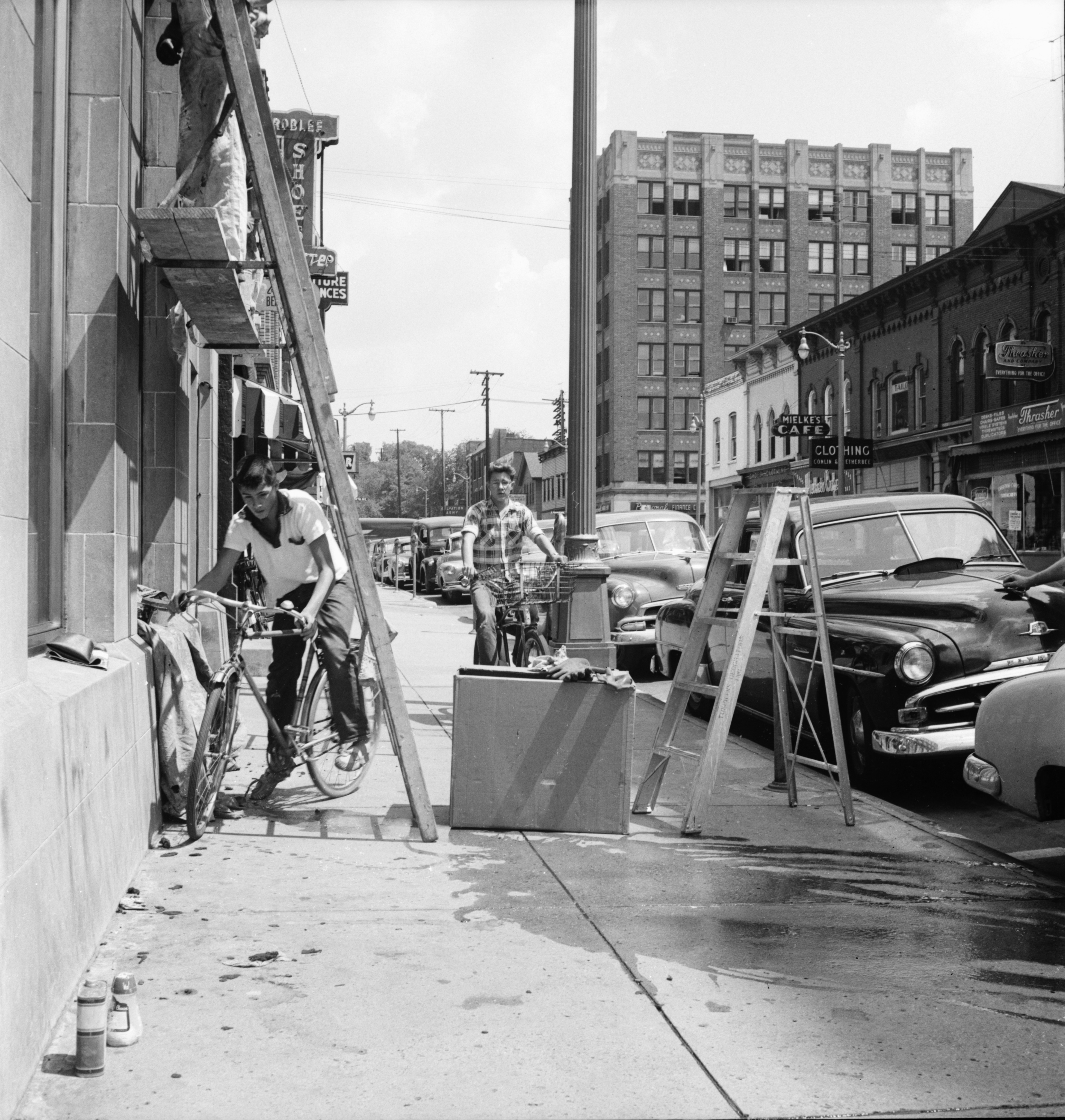 John Lopez guides his bike under a ladder outside State Savings Bank, 103 Washington St., August 1954 image