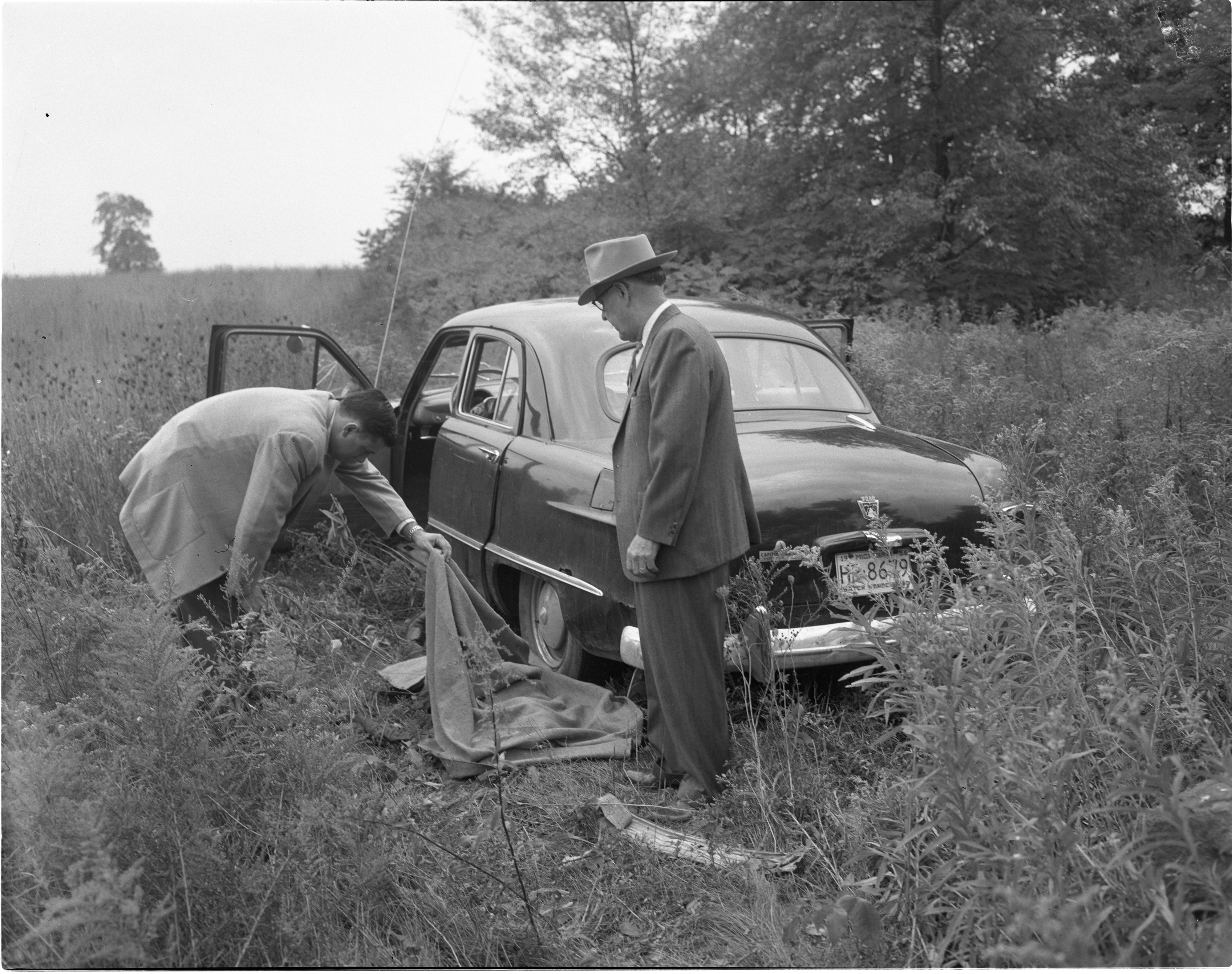 Undersheriff Charles Shaw & Detective Lt. Melvin Fuller Examine The Body Of Dell Cain In Willow Village, September 1956 image