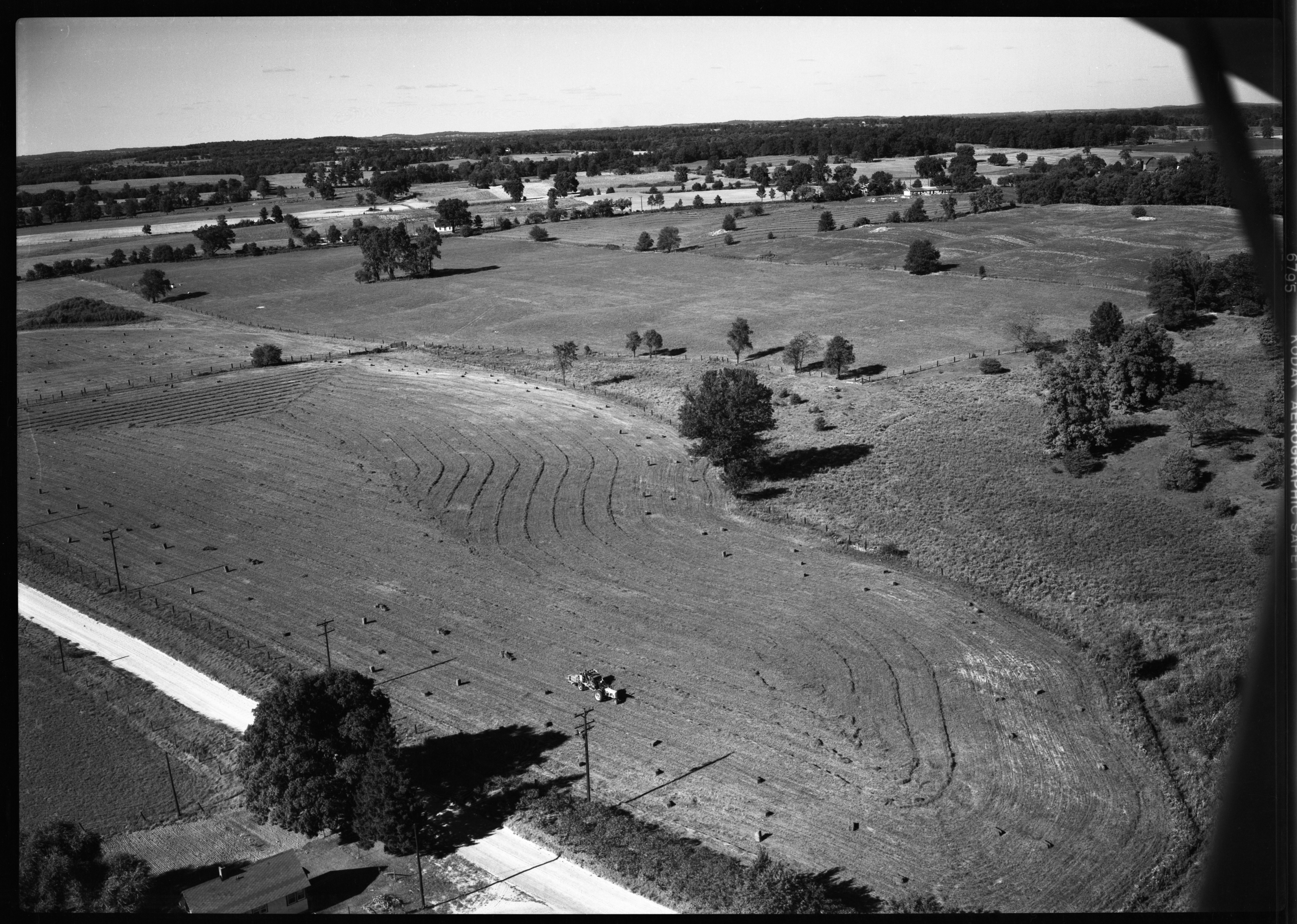 Aerial Photograph of Farmer Cutting Hayfield, September 1949 image