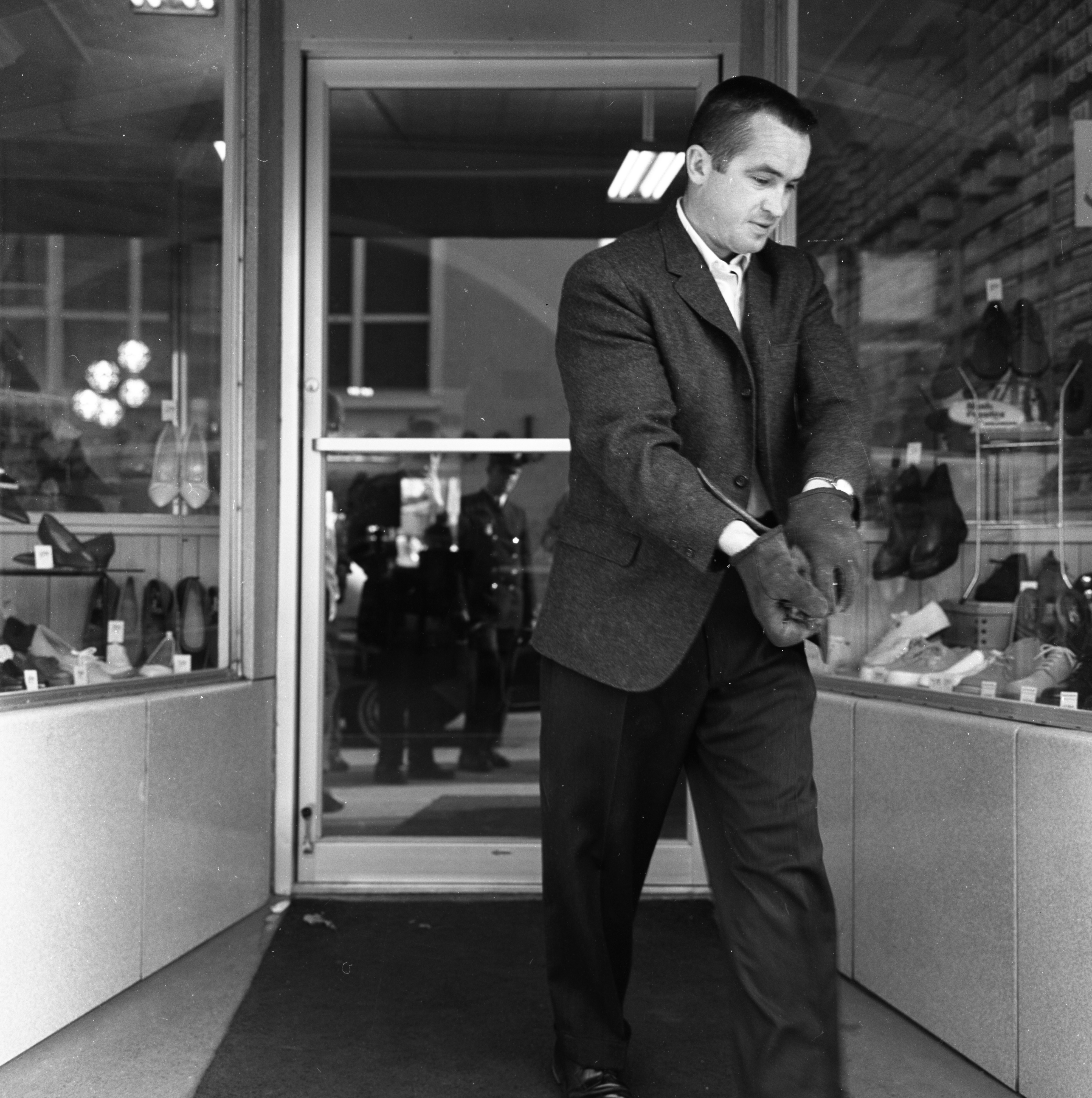 Jim Mynning Carries Muskrat Found at Doorway of Mast Shoe Store on Liberty St., March 1964 image