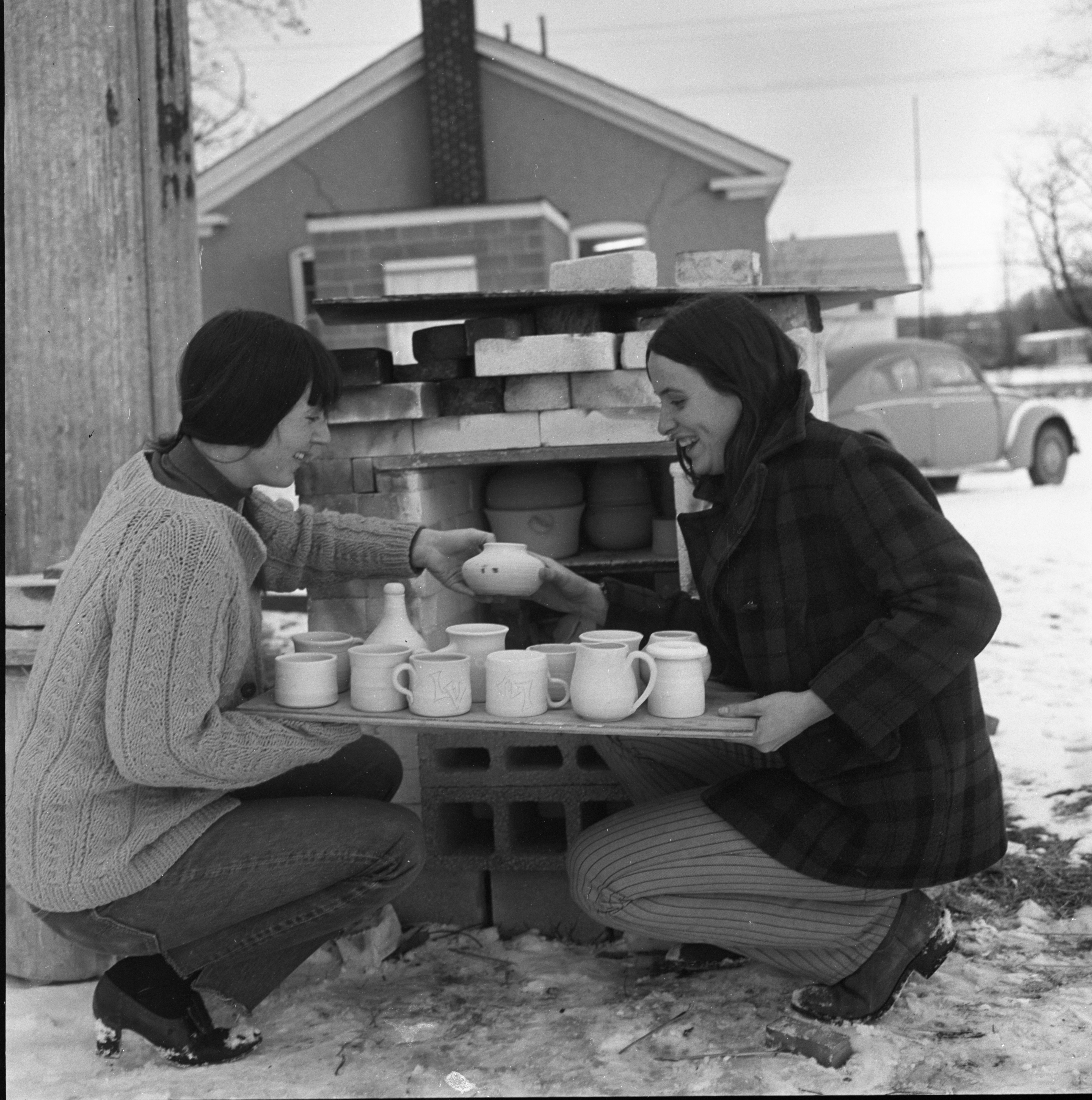Ginny Conrow & Nancy Steege Tend The Kiln Behind The Schoolhouse Pottery Studio, December 1969 image