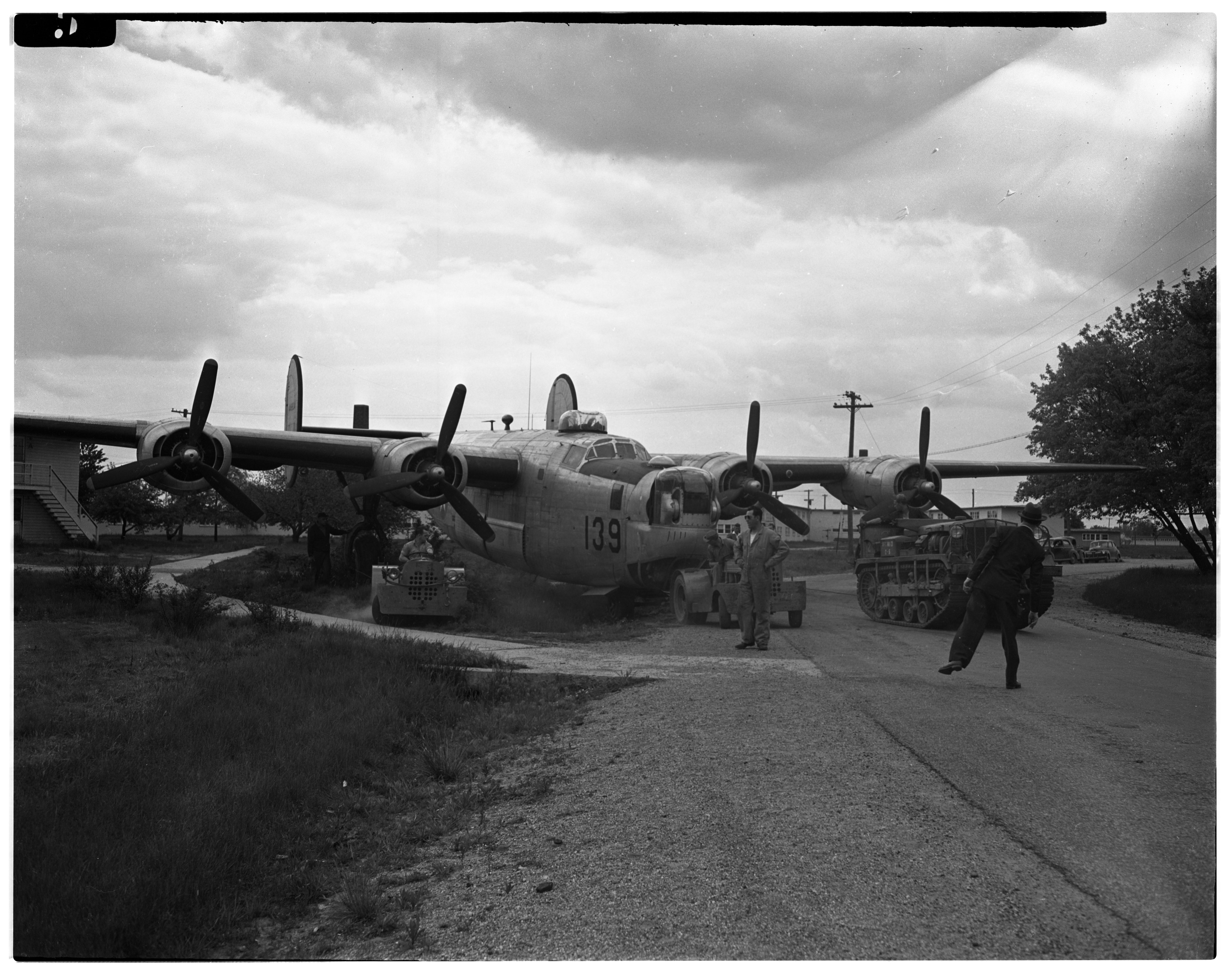 B-24 Bomber #139 hauled through streets of Willow Village to serve as war memorial in front of the Edsel B. Ford post of the American Legion at 2094 E. Michigan Avenue, Ypsilanti, May 1946 image