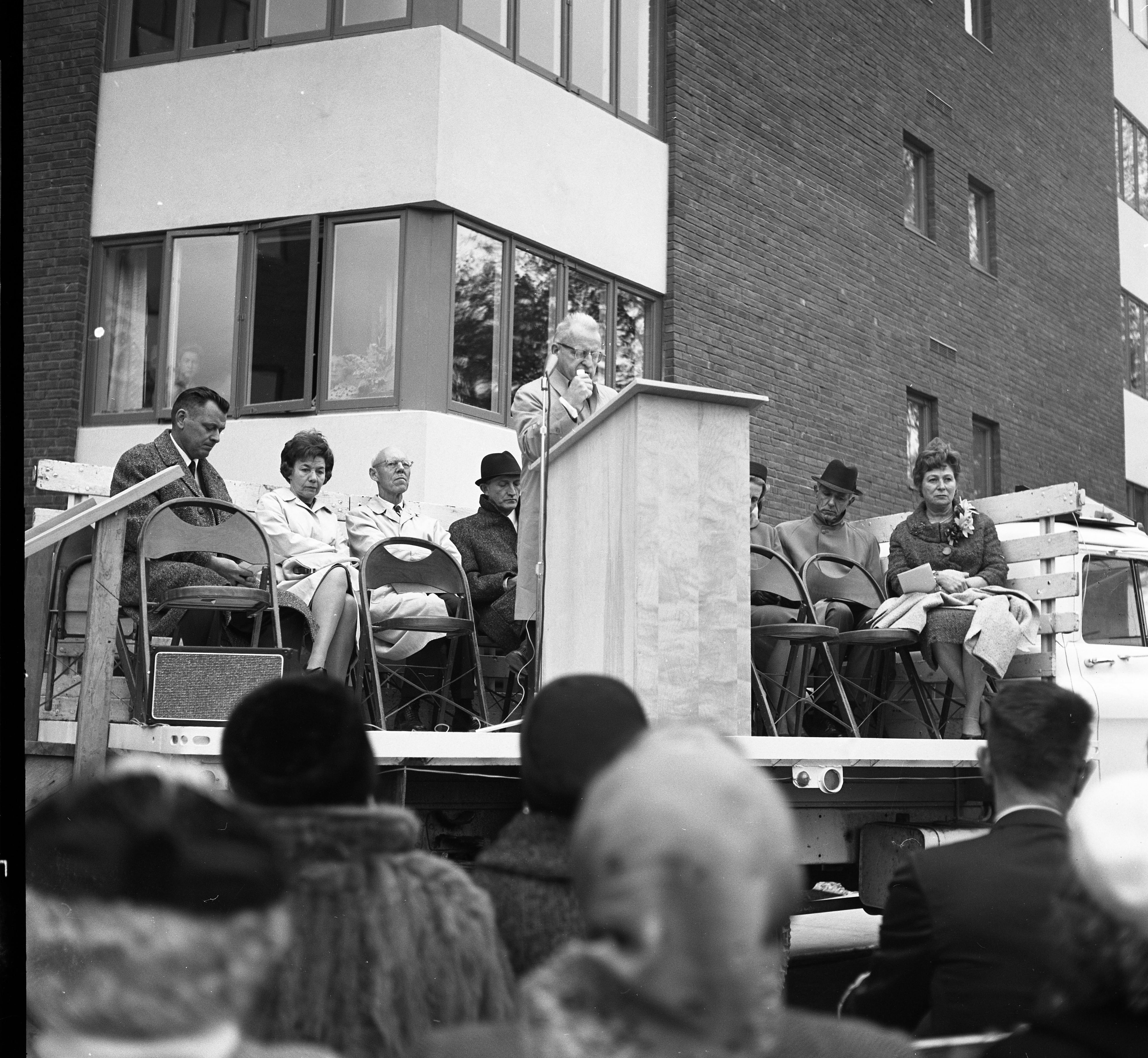 Speakers Huddle Against The Cold, Wet Weather At Dedication of Lurie Terrace, October 1964 image
