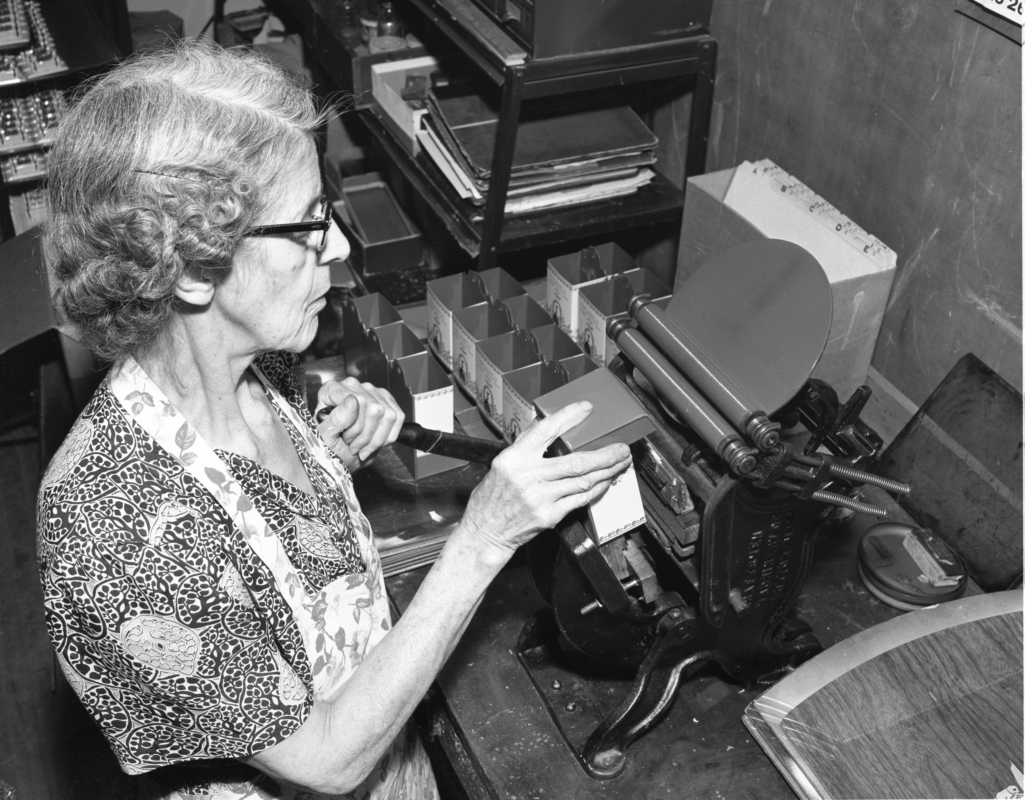 Edna Cook Uses A Printing Press At Advertisers Publishing Co., October 1954 image