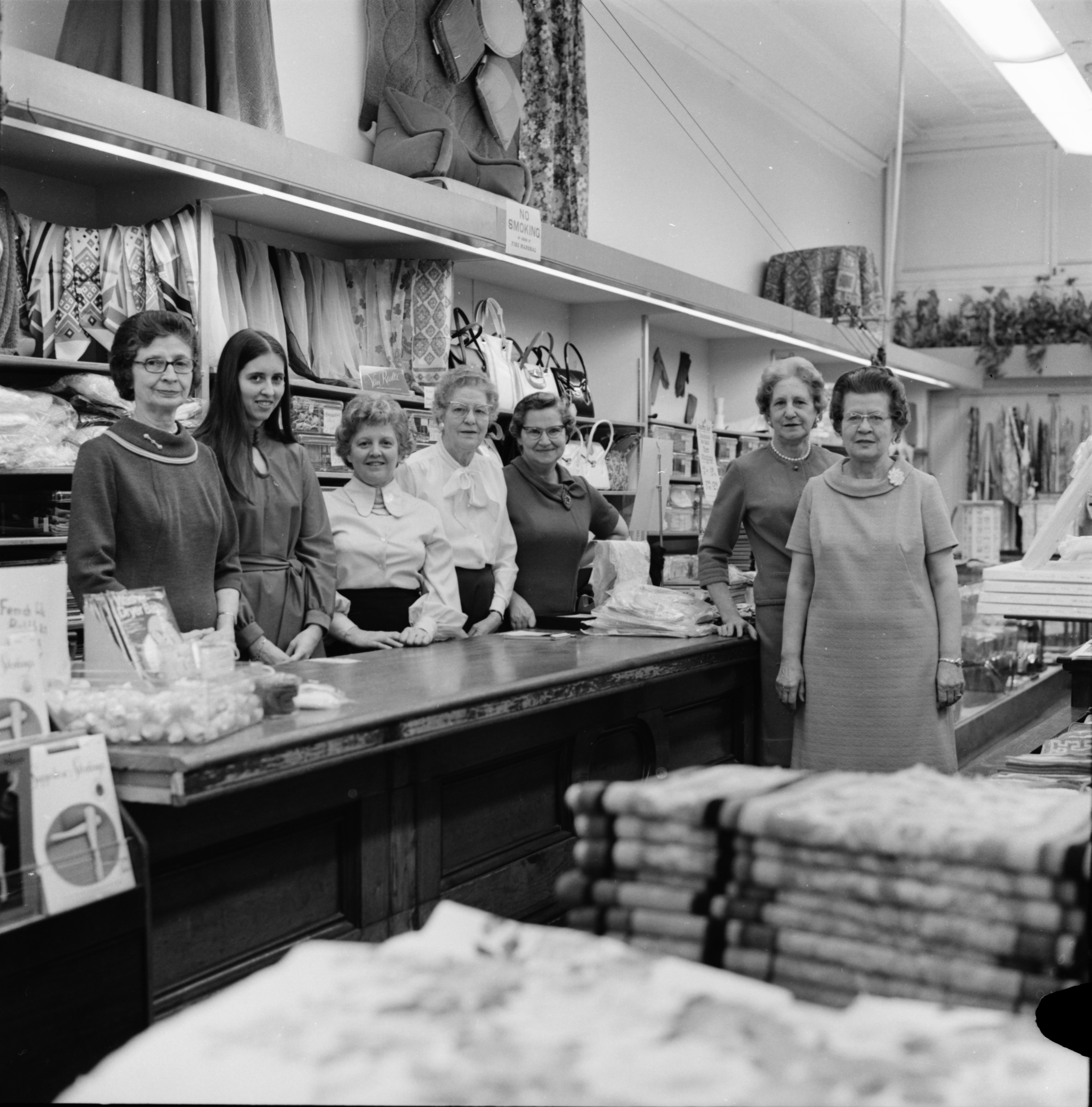 Employees in the Accessories, Linen and Notion Department pose for B. E. Muehlig, Inc.'s 60th Anniversary advertisement, March 1971 image