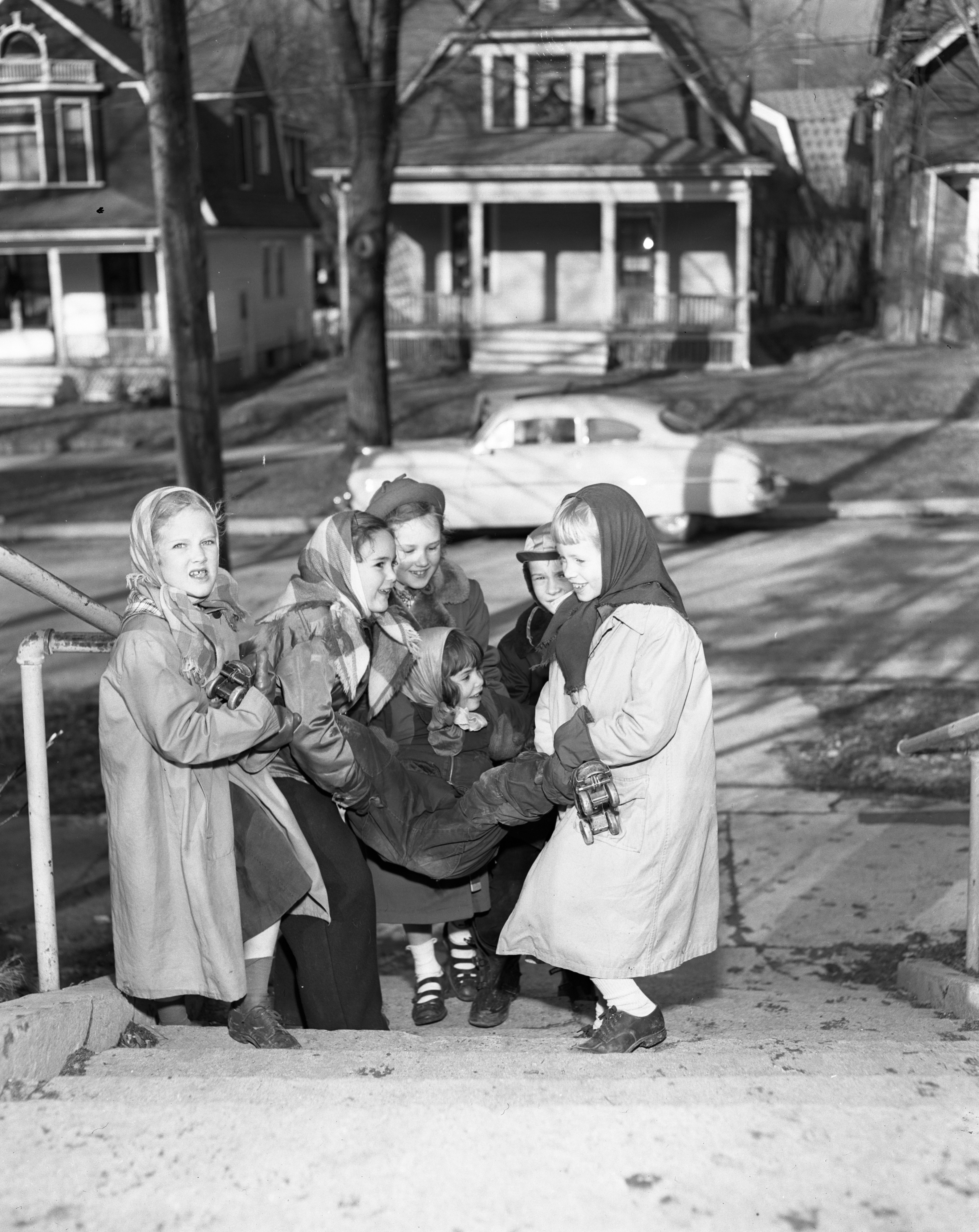 Angell School children carry playmate with rollerskates up the steps, January 1951 image
