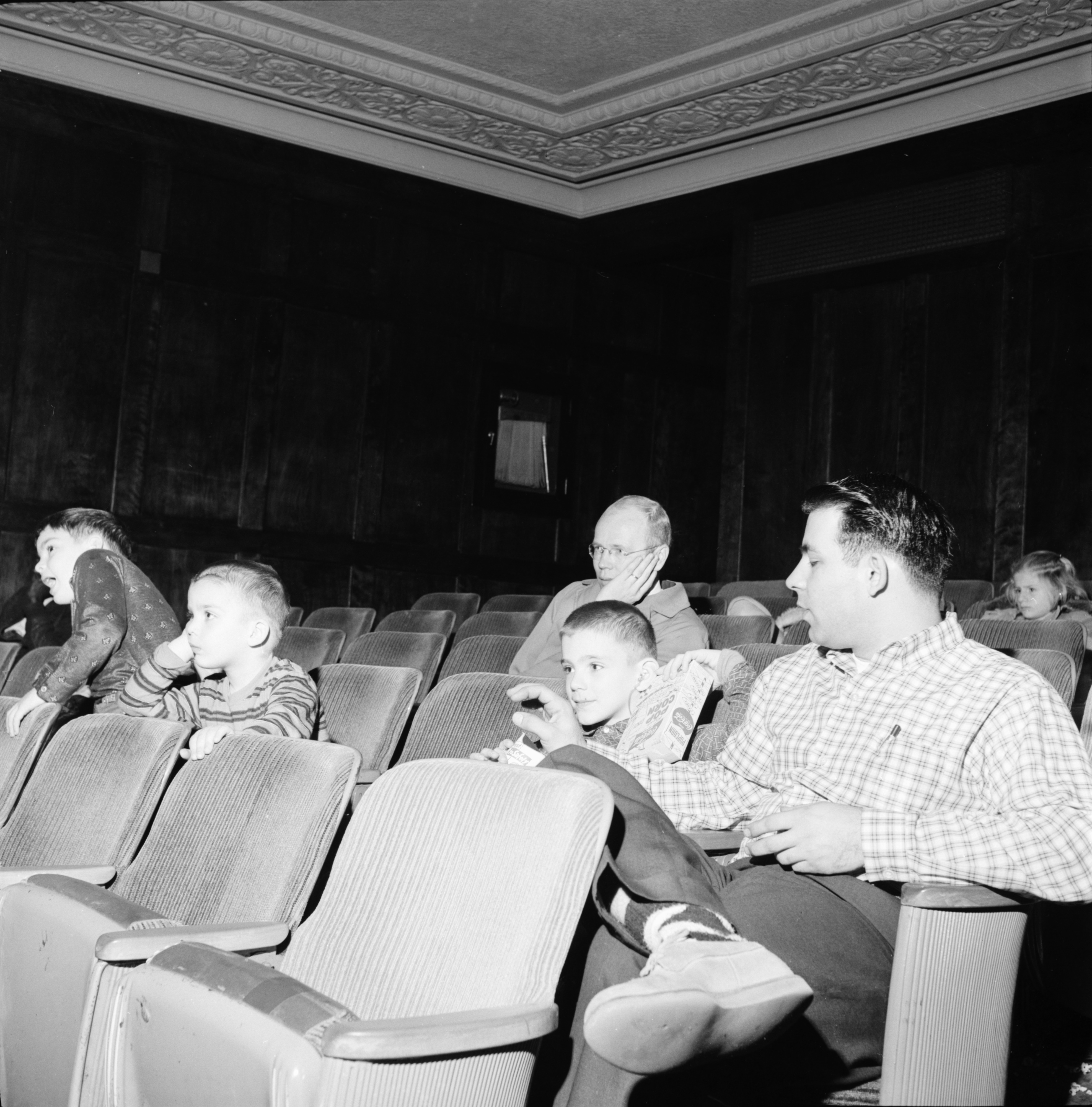 Ann Arbor News reporter Bill Treml watching cartoons at the Michigan Theater with kids, November 1960 image