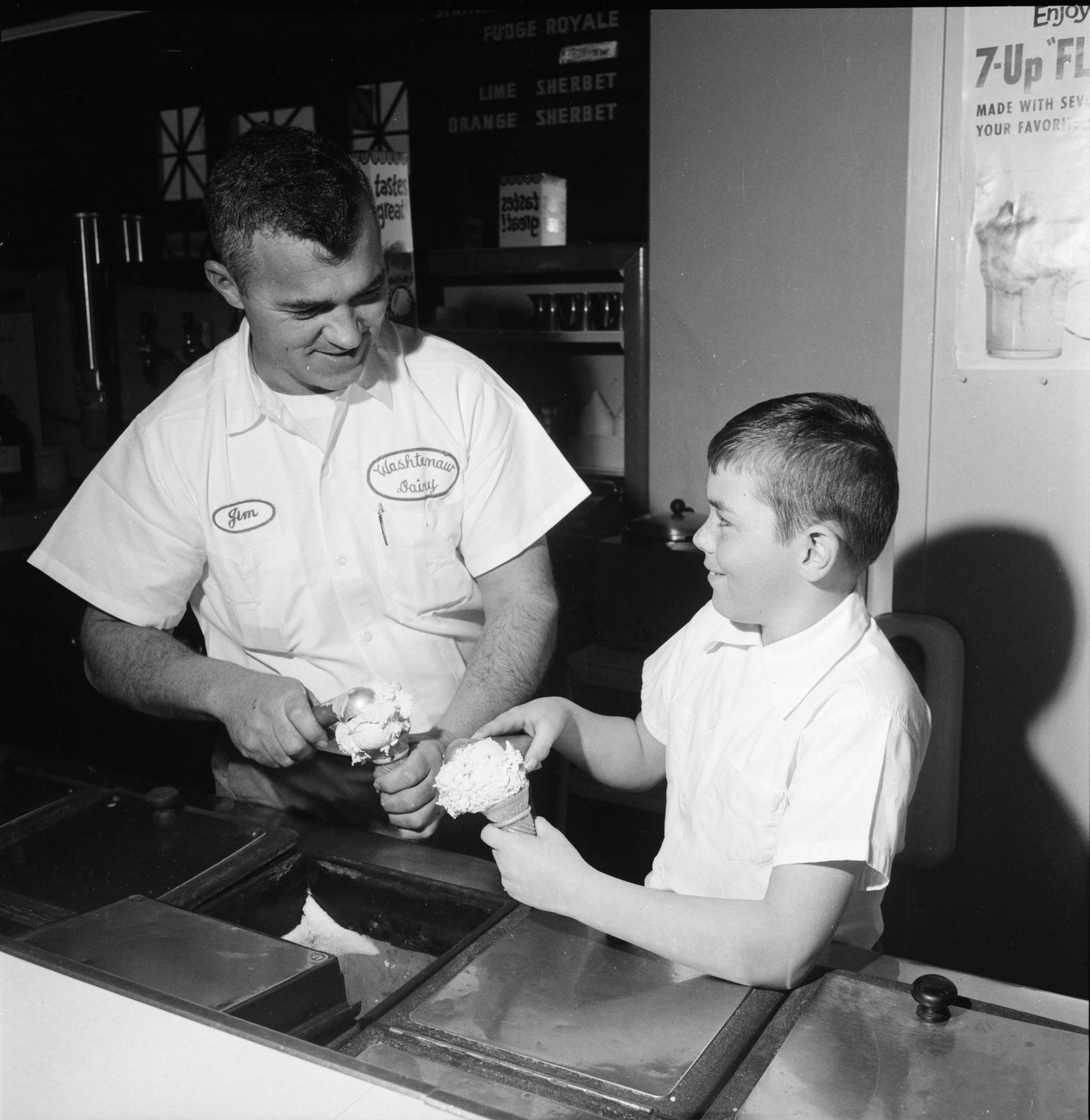 Jim Smith, Jr. learns to mount a scoop of ice cream from his dad, February 3, 1962 image