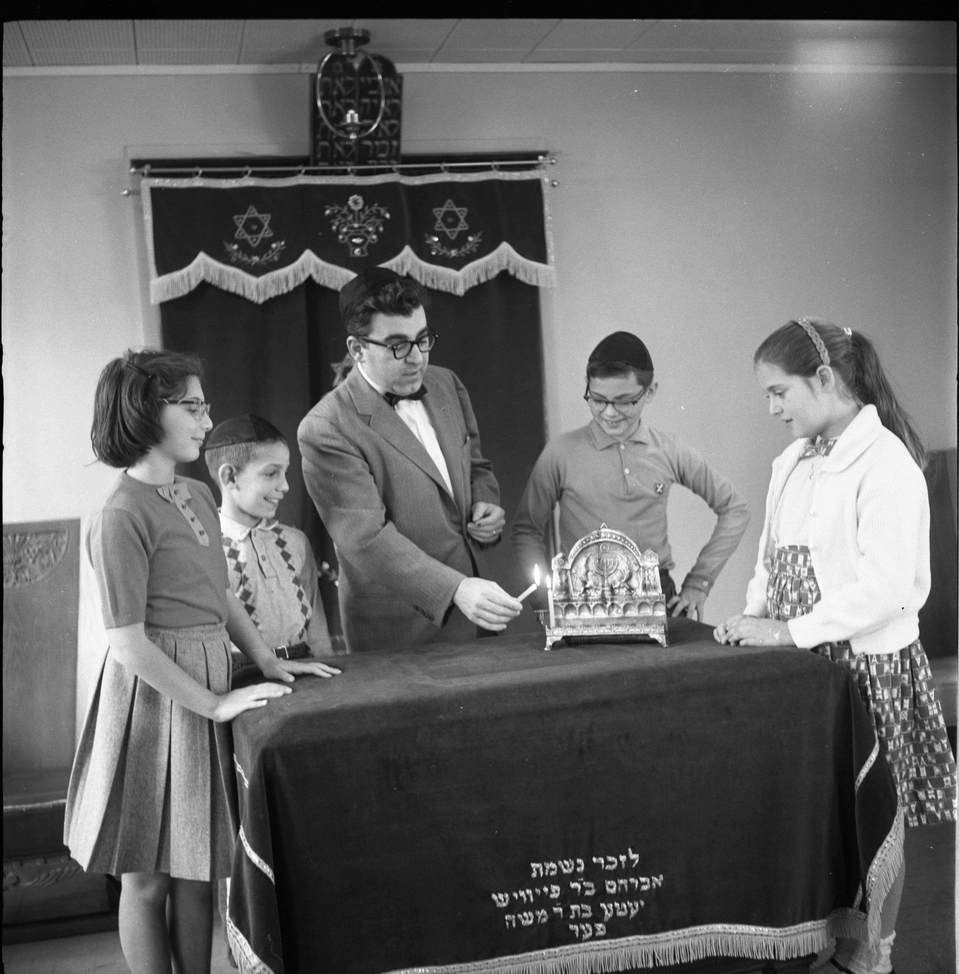 Rabbi Julius Weinberg Lights The First Candle For Hanukkah With Children Watching, December 1960 image