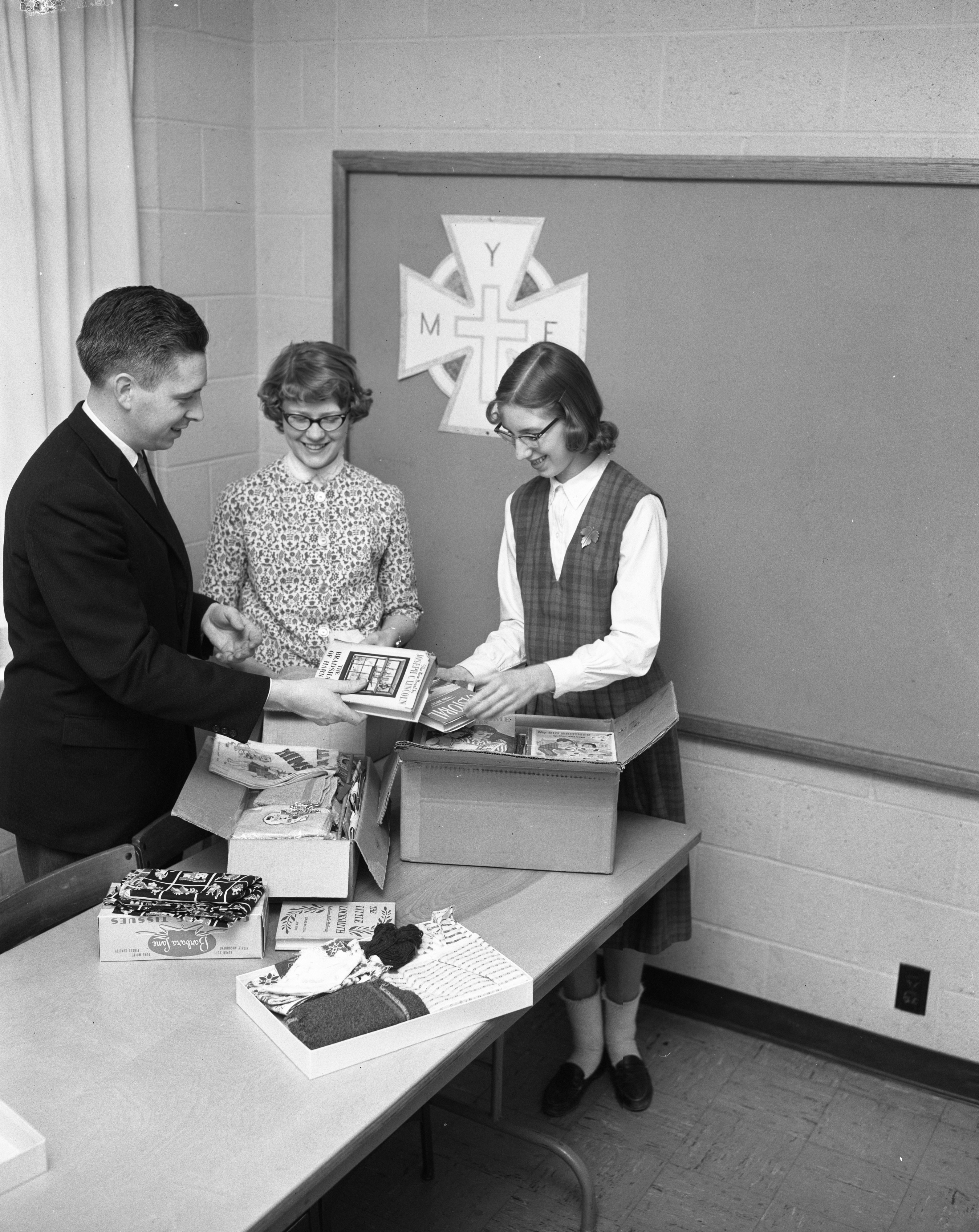 Rev. Kendall Cowing, Katie Strand and Laura Van Vlack Pack Books for Marcy Center, First Methodist Church, March 1961 image