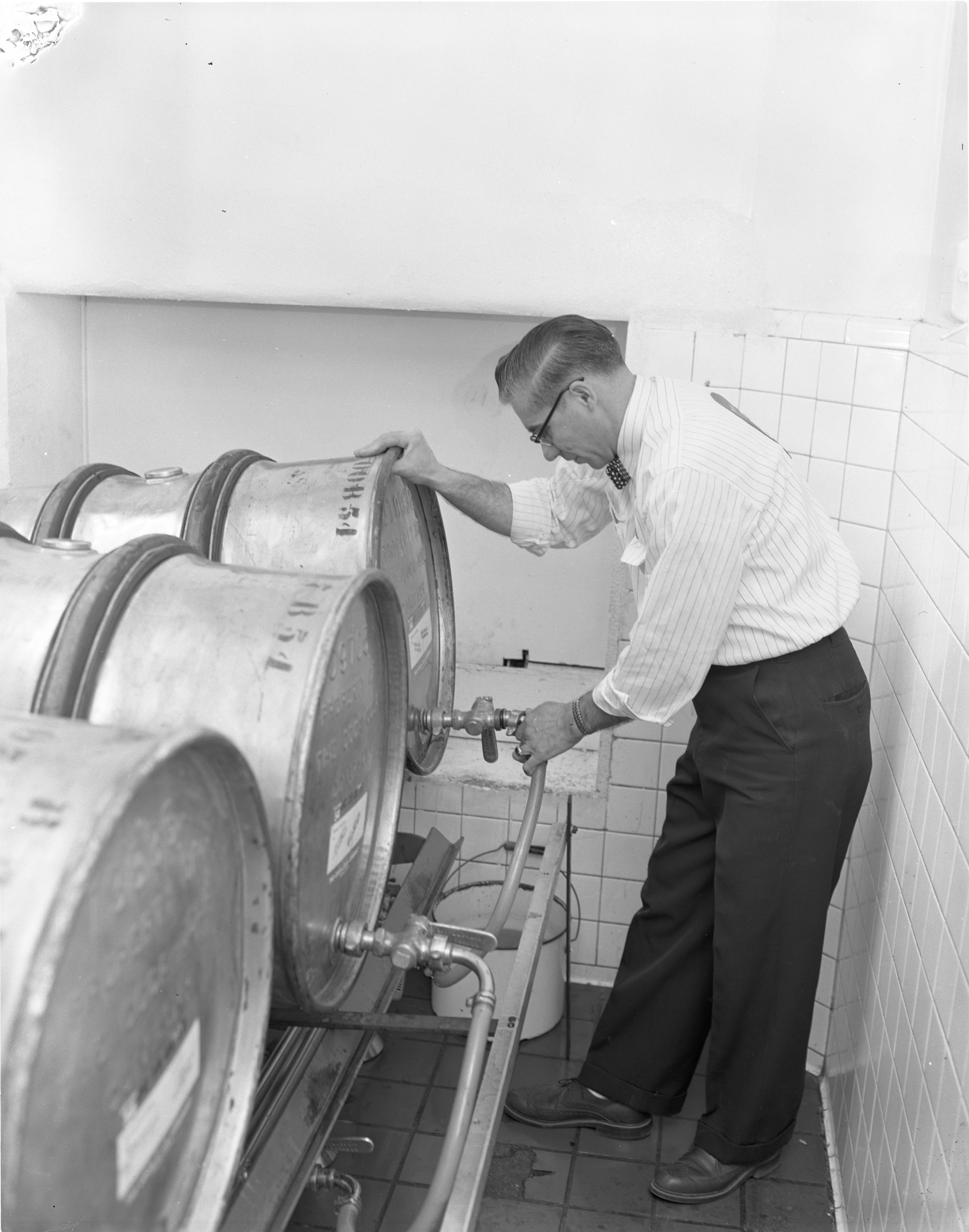 An Employee Tends To Steel Barrels Of Coca-Cola Syrup At The Kleis Beverage Co., January 1956 image
