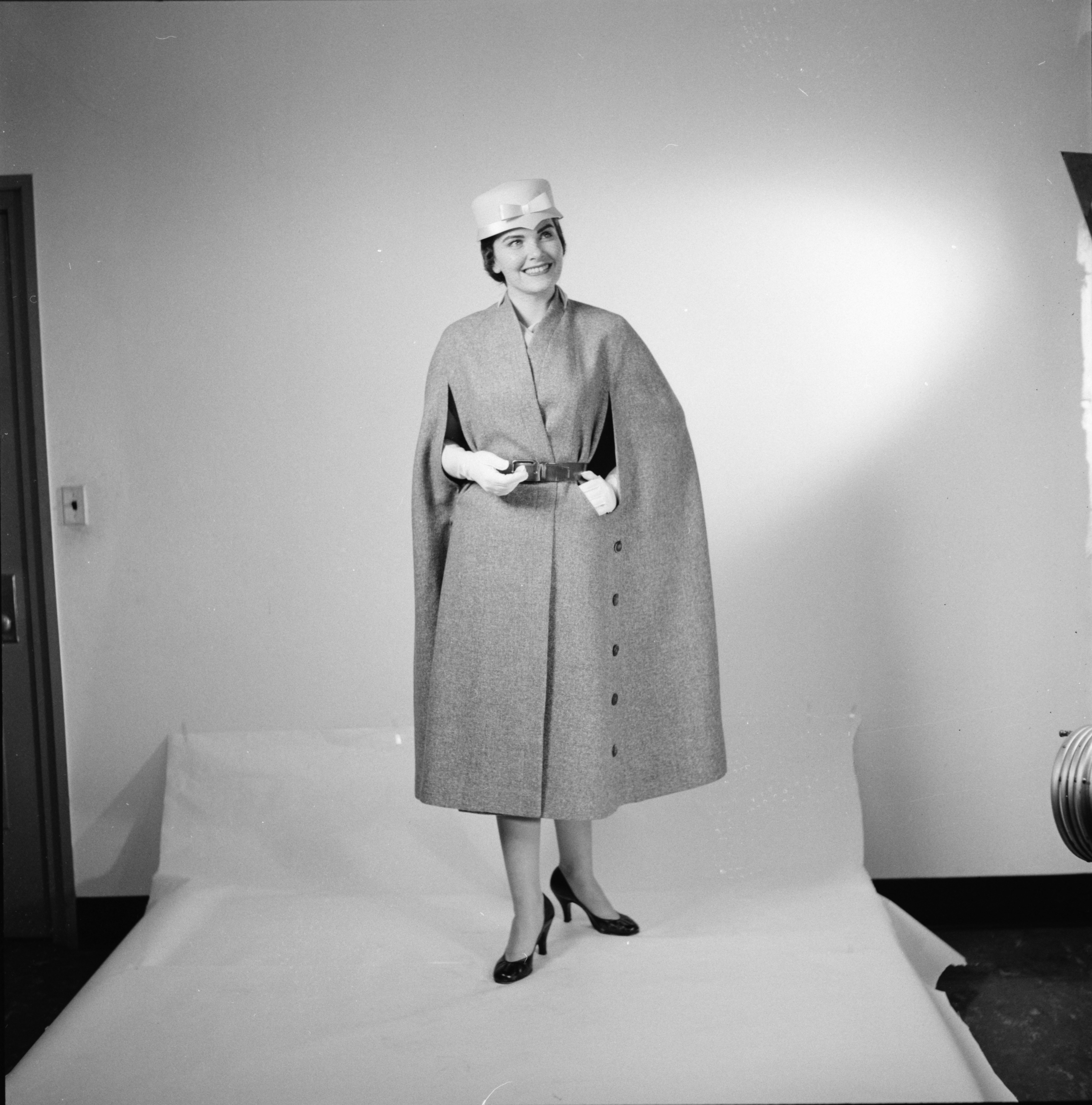 Harriet M. Rose models a cape and jacket in the Michigan Dames' Fashion Show, March 1957 image
