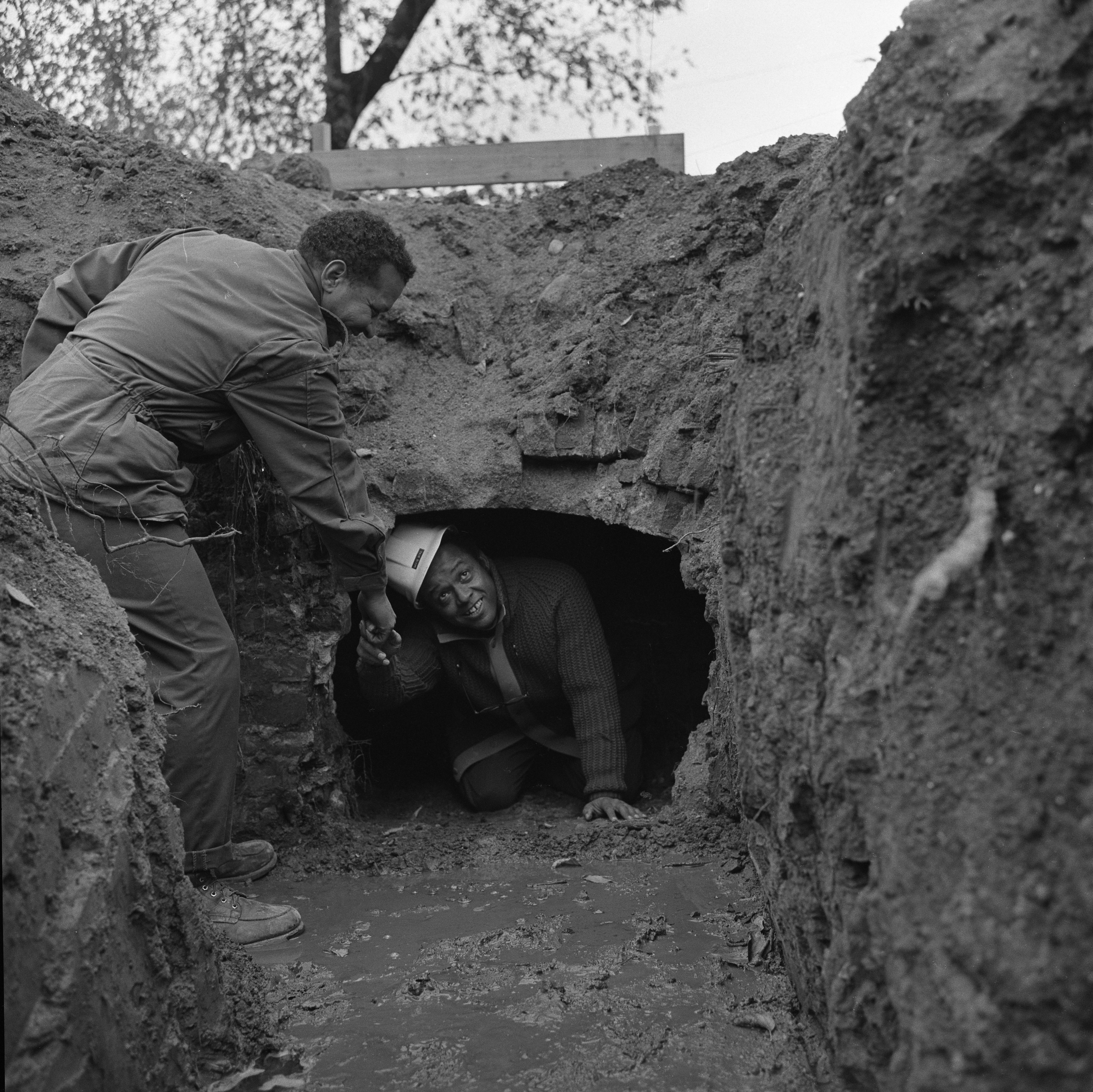 Donald Calvert Helps David R. Byrd Exit Possible Slave Tunnel Discovered Under Washtenaw Lumber Building, November 1972 image
