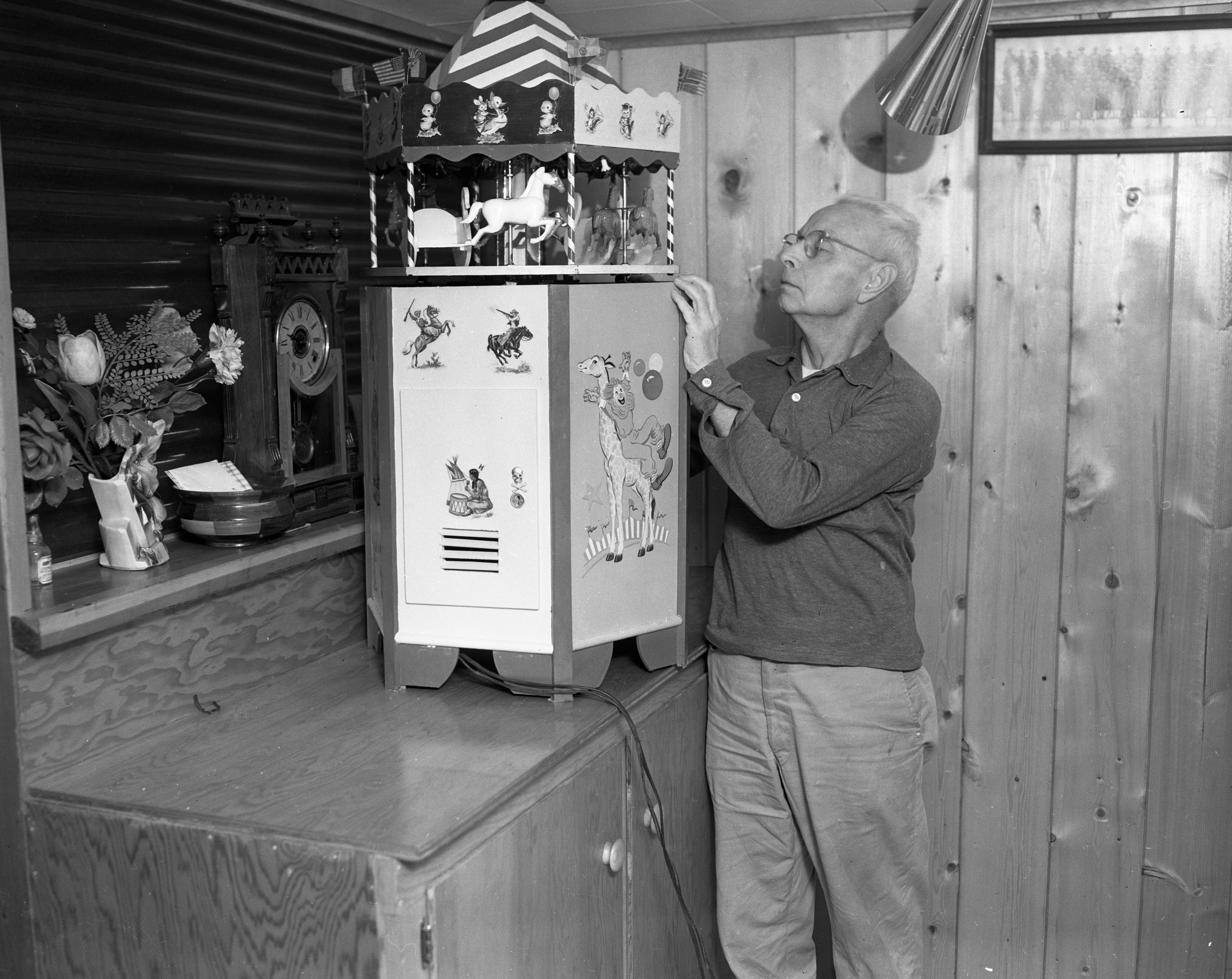 Ernest Mack makes a merry-go-round for his grandchildren, December 1963 image