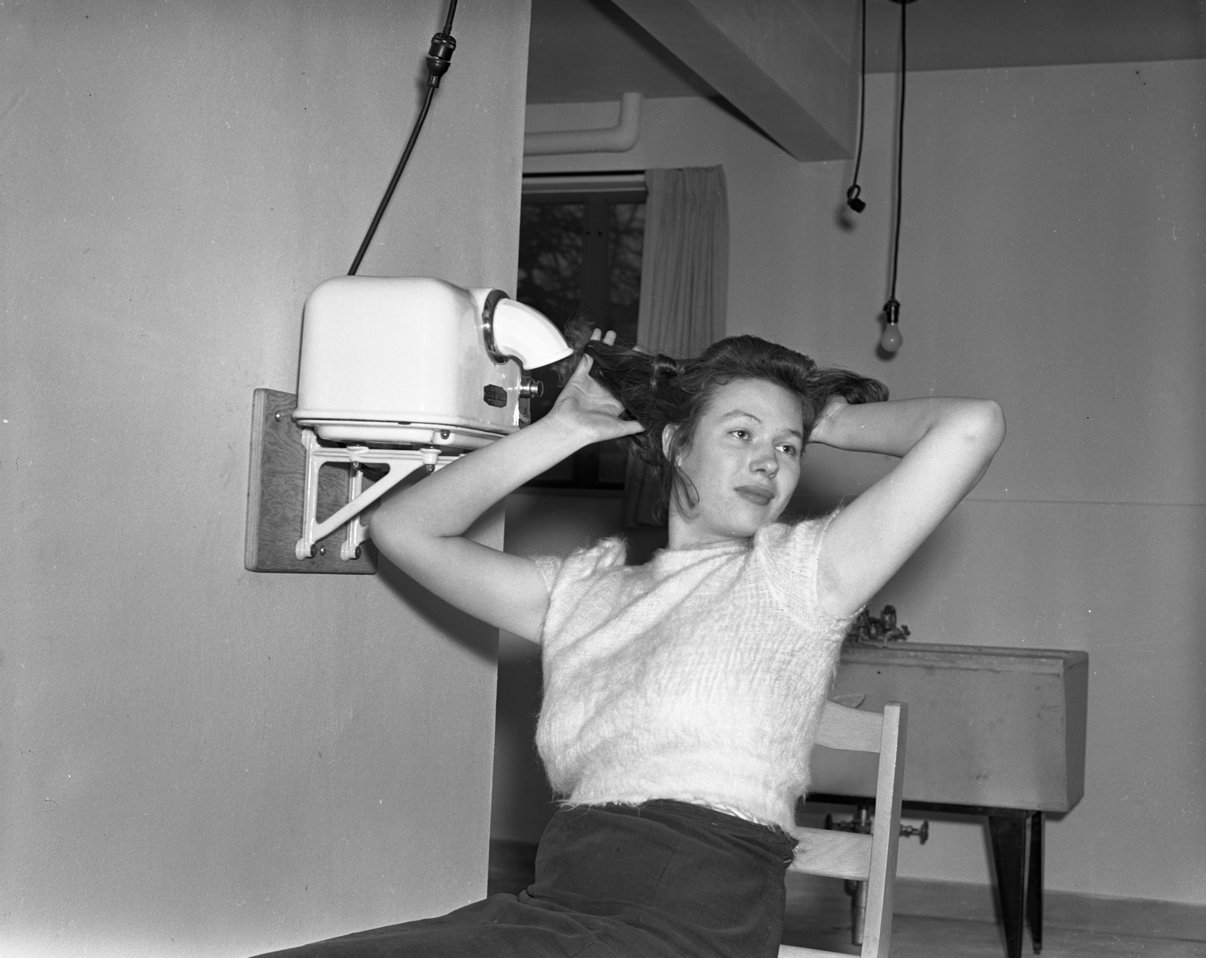 Girl with new hair dryer in Michigan State College dorm, undated image