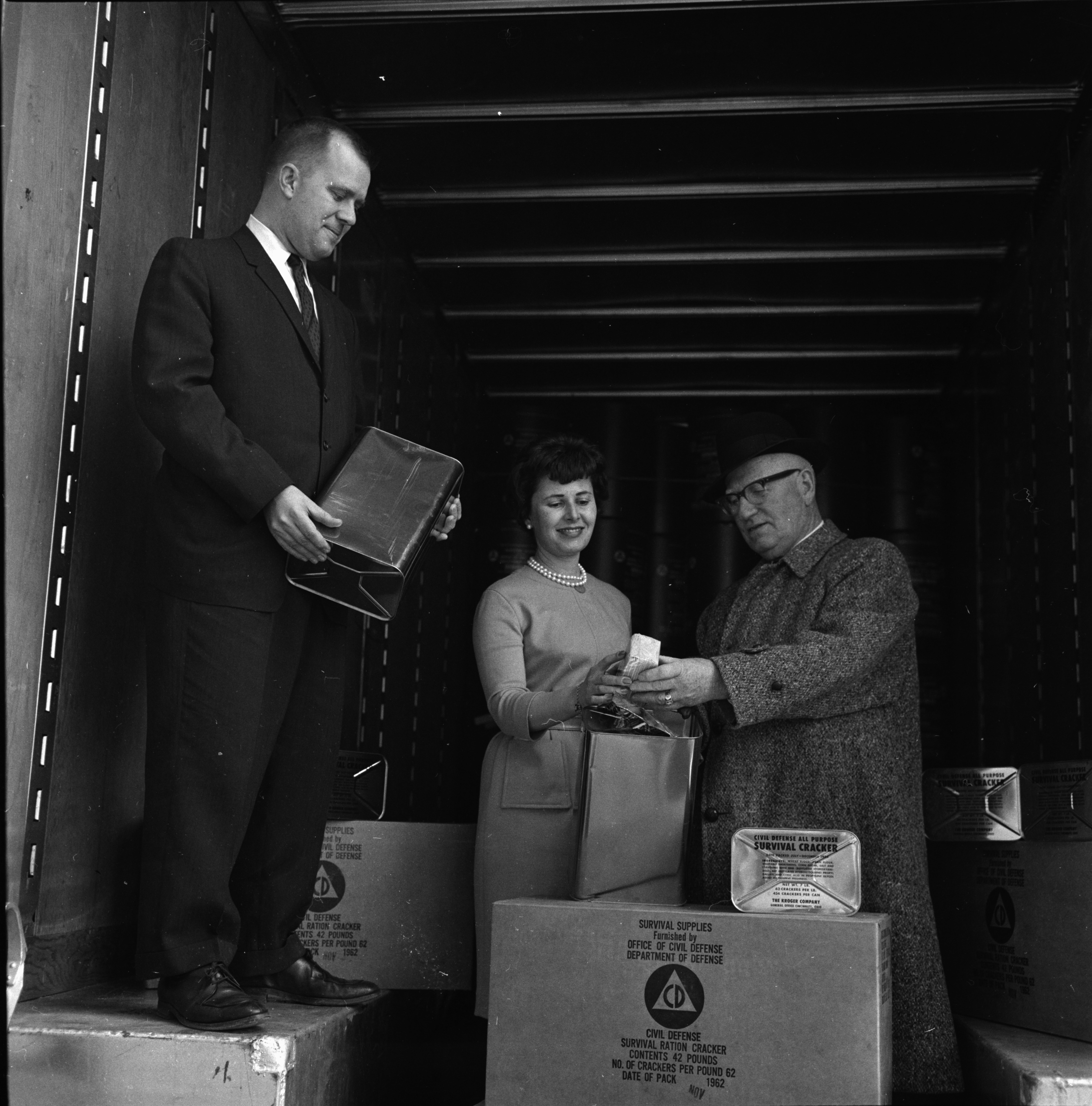 Sally Beightol and H. R. Shipman inspect supplies for fall-out shelter at Huron Towers, March 1963 image