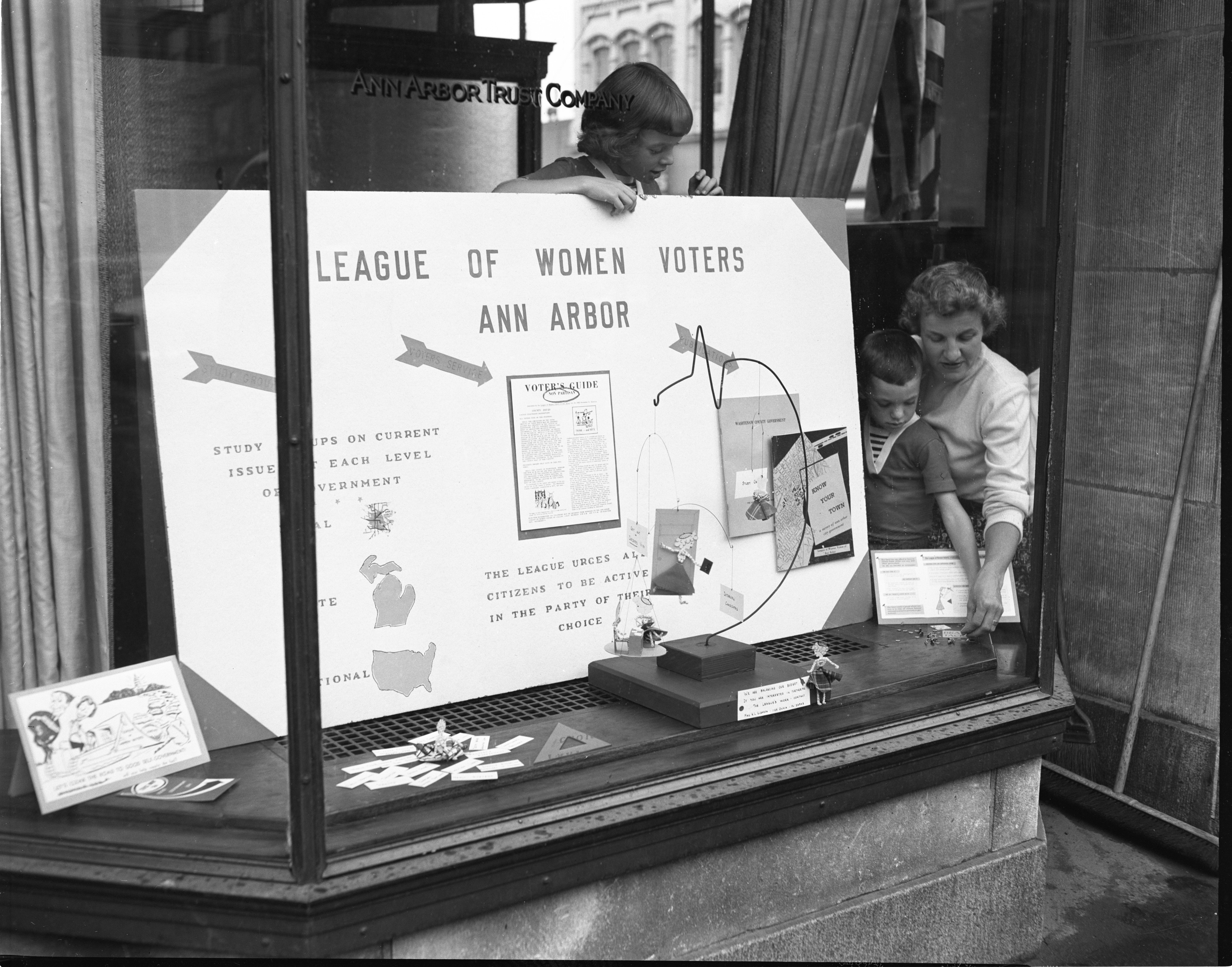 Sunny Morse & Her Children Assemble A League Of Women Voters Window Display In The Ann Arbor Trust Building, September 1953 image
