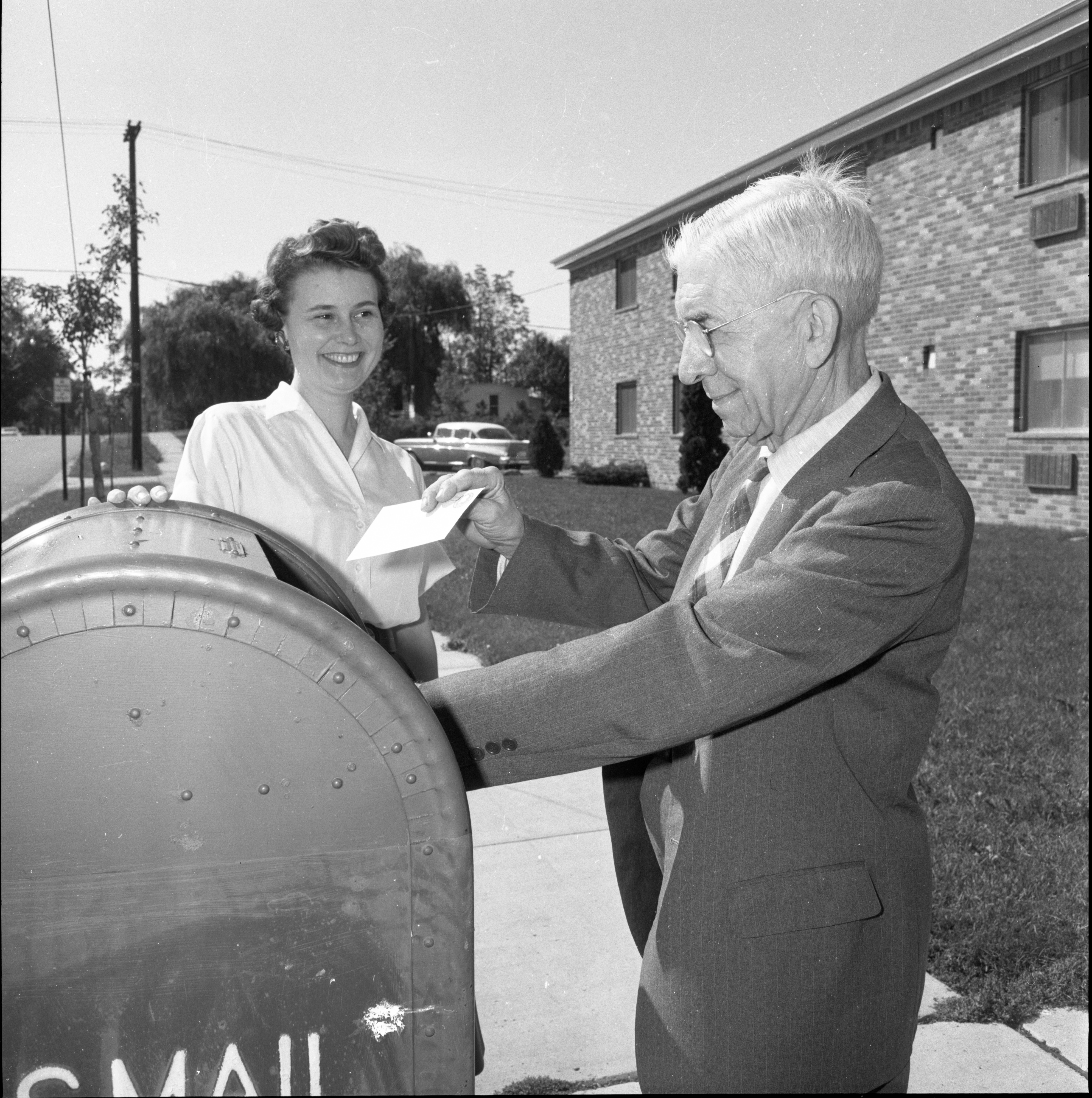 Dr. John F. Shepard Drops A Financial Contribution For The Ann Arbor League Of Women Voters Into A Mailbox, September 1962 image