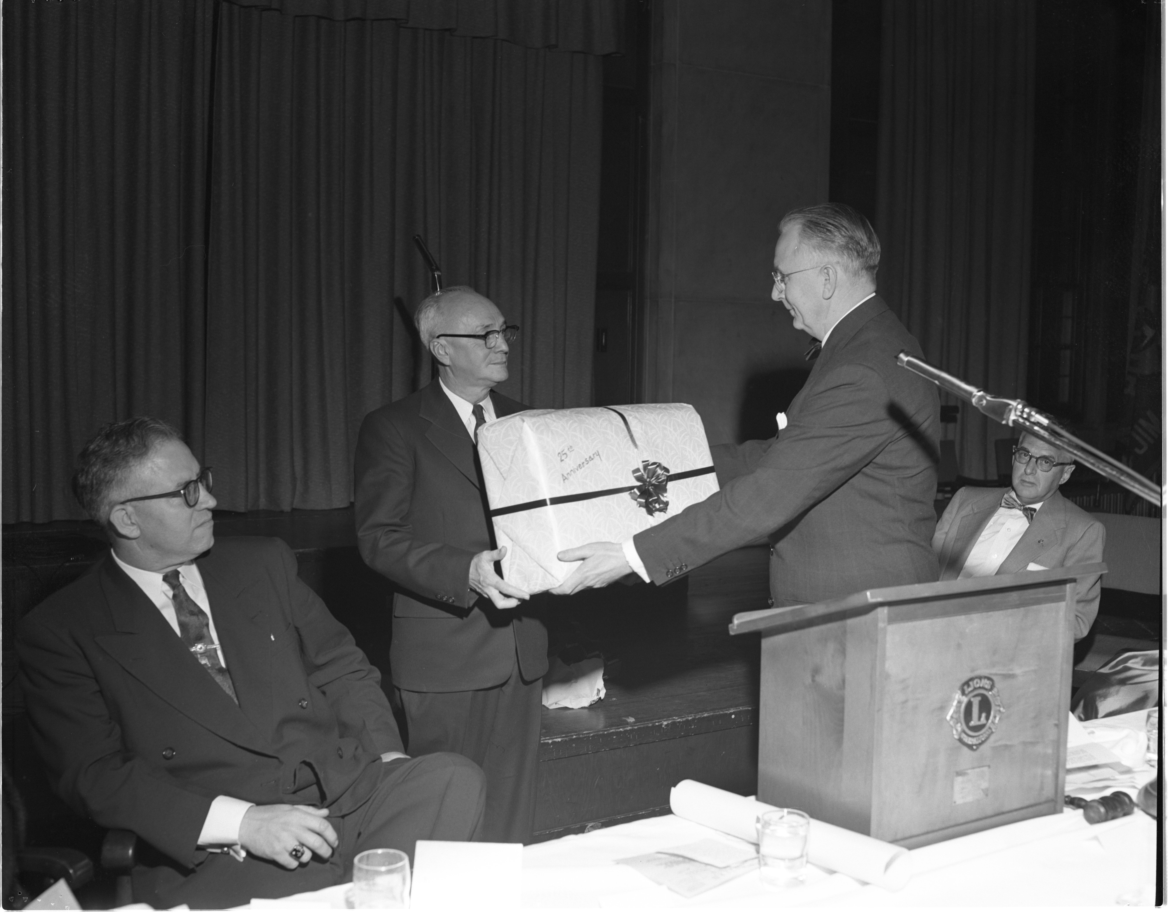 Harold C. Baker Receives A Gift At The Ann Arbor Lions Club 25th Anniversary Party, May 1954 image