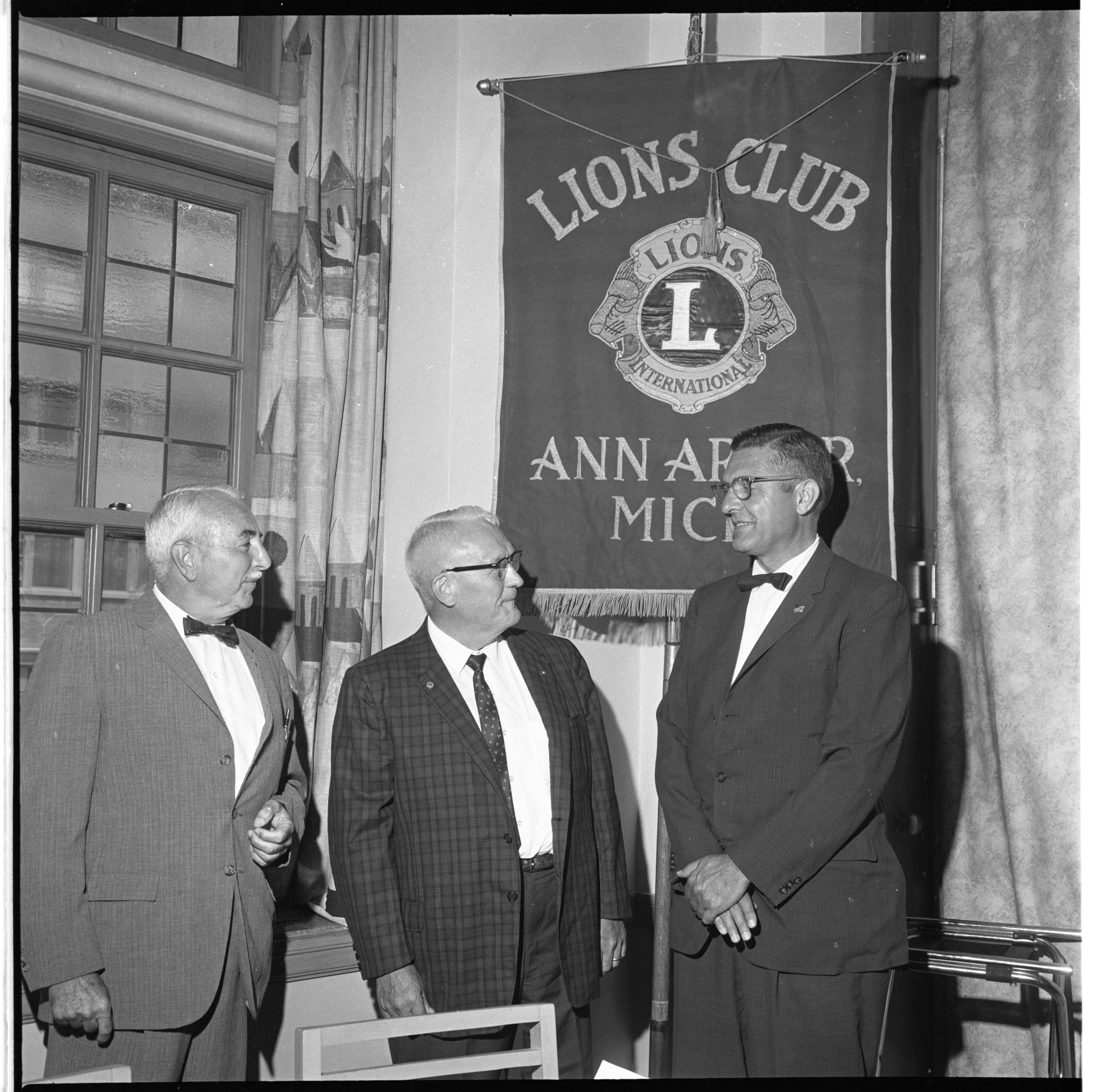 Robert Austin, Dr. Ted Hunter, & Dr. John Henderson Discuss The Michigan Eye Bank At An Ann Arbor Lions Club Event, July 1964 image