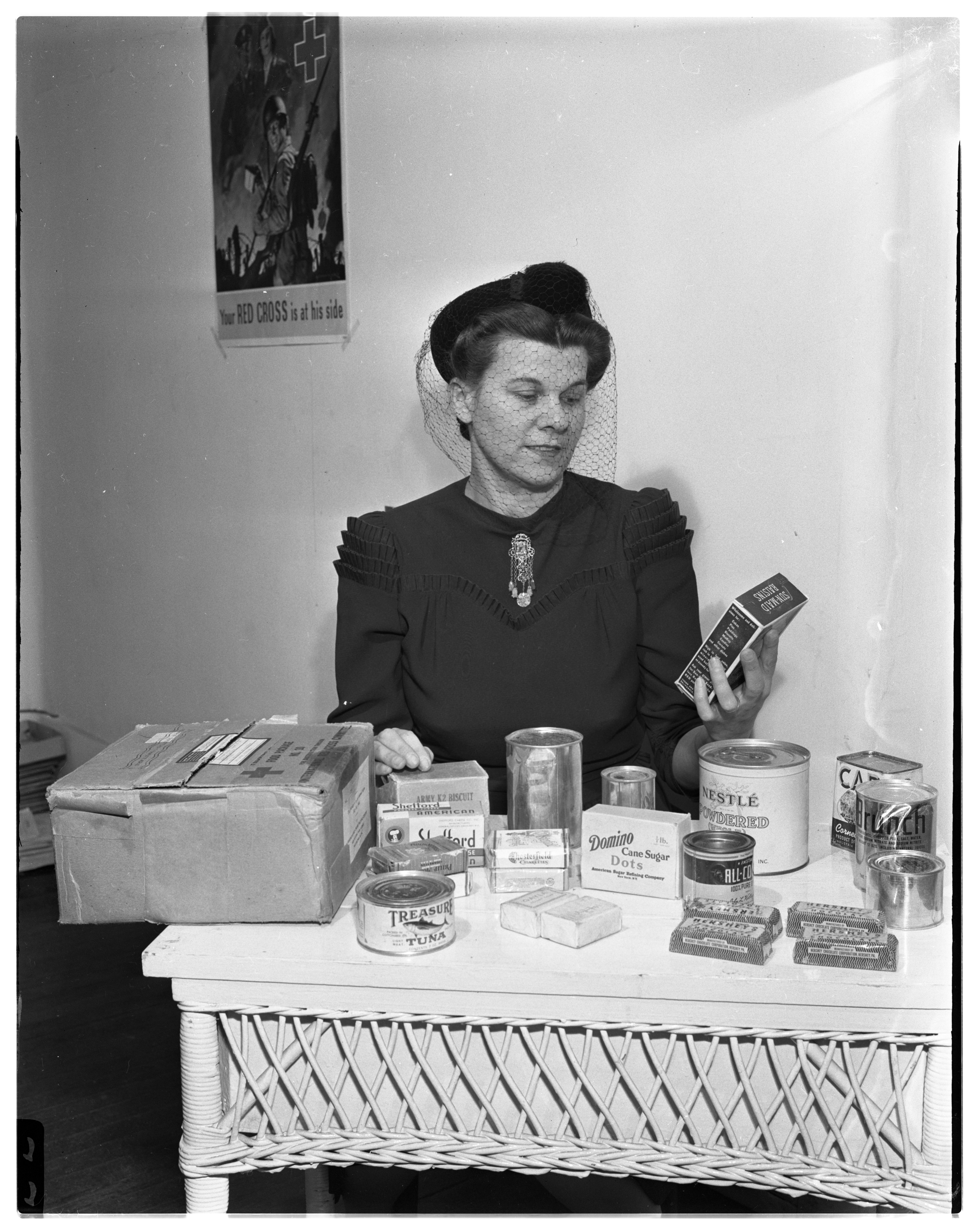 Irene Dumond packs Red Cross package for her son Jack, a POW, March 1944 image