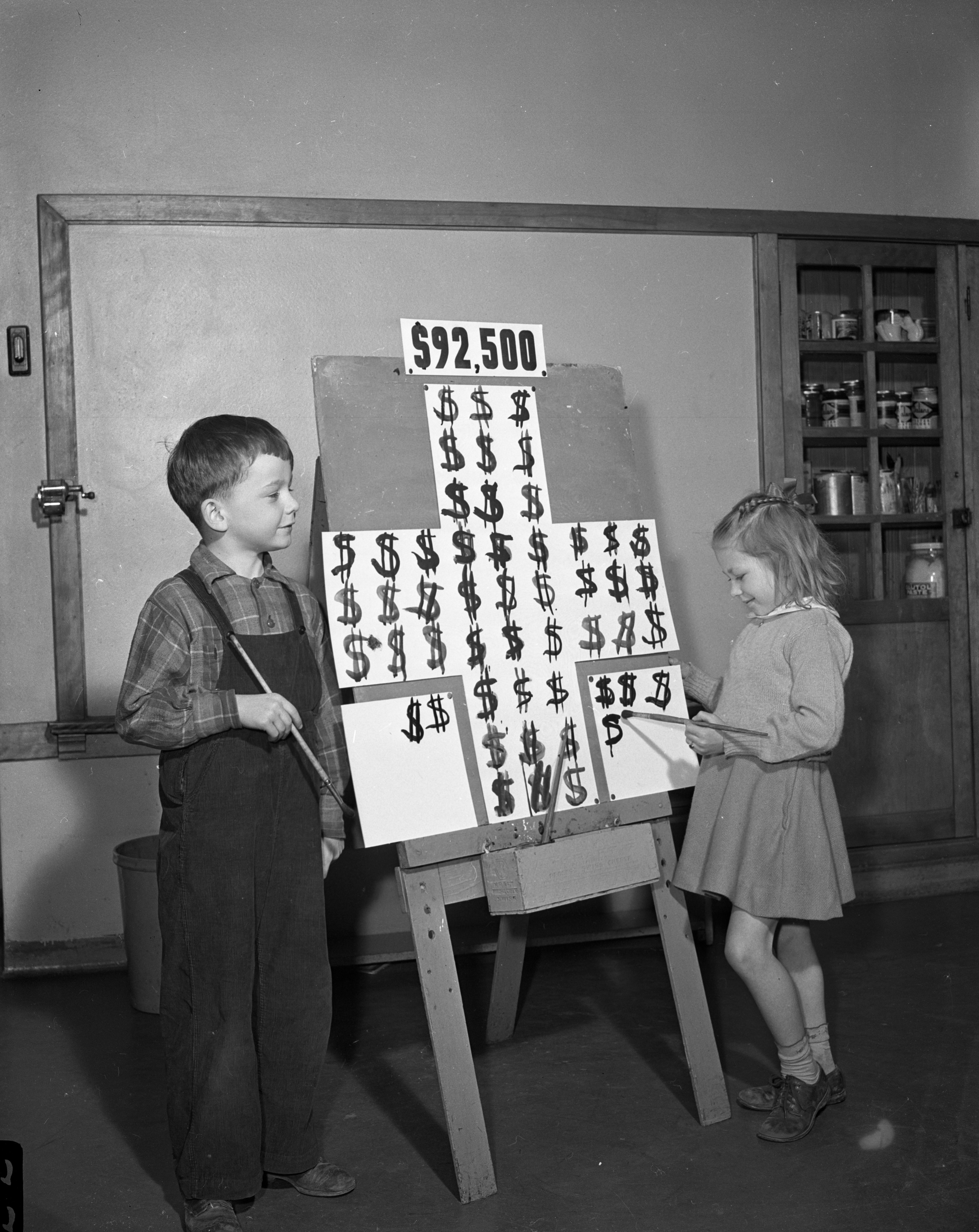 Campbell Smith (representing Ann Arbor) and Saundra Wares (representing the county outside Ann Arbor) Show the Red Cross Drive's Daily Score, March 30, 1944 image