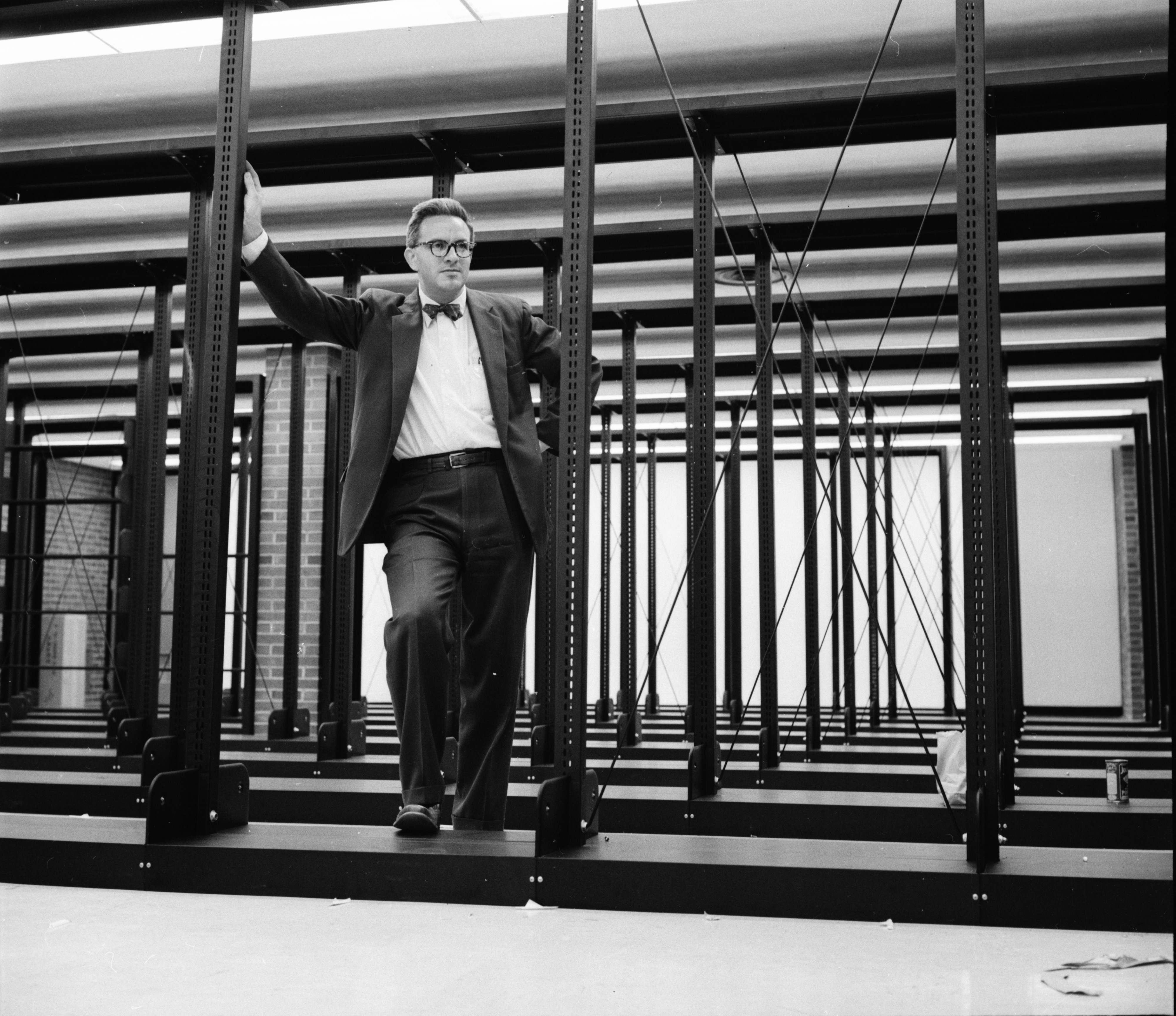 Library Director Homer Chance Standing Amid Shelving in New Ann Arbor Public Library, October 1957 image