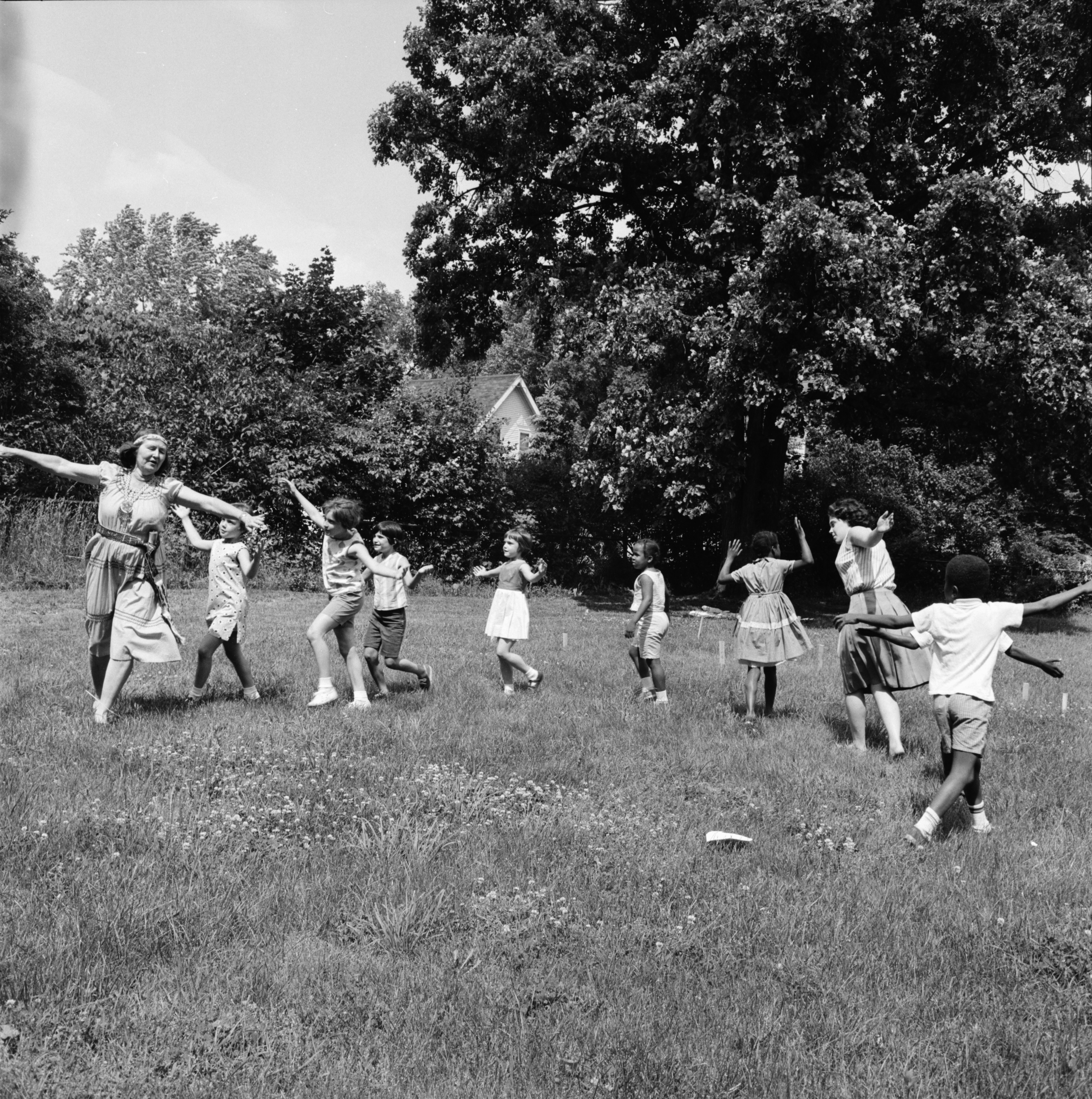 "Teachers lead children in a ""Snake Dance"" at Mack School, June 1966 image"