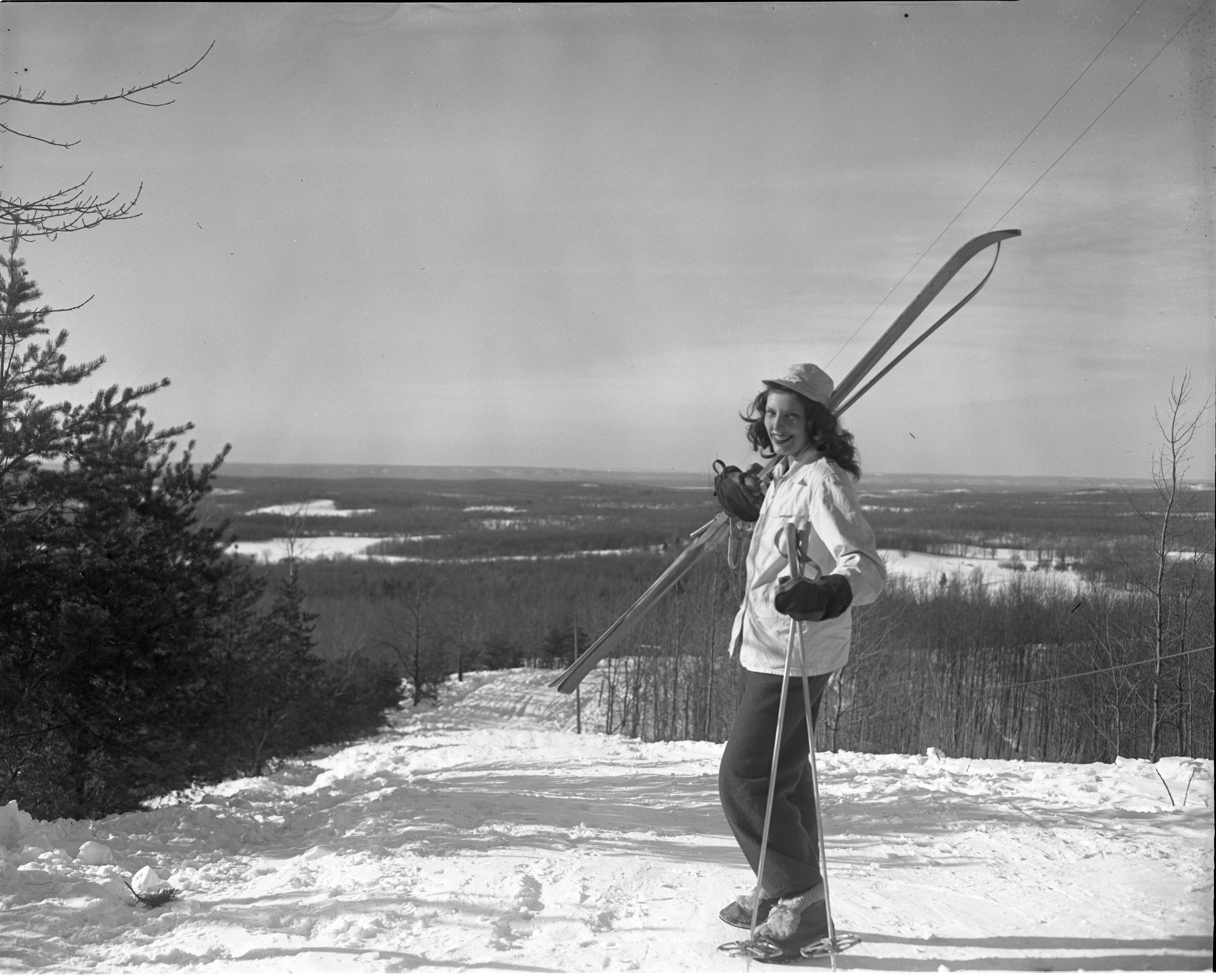 Skier Poses With Her Skis Over Her Shoulder At Caberfae In Cadillac, February 1946 image